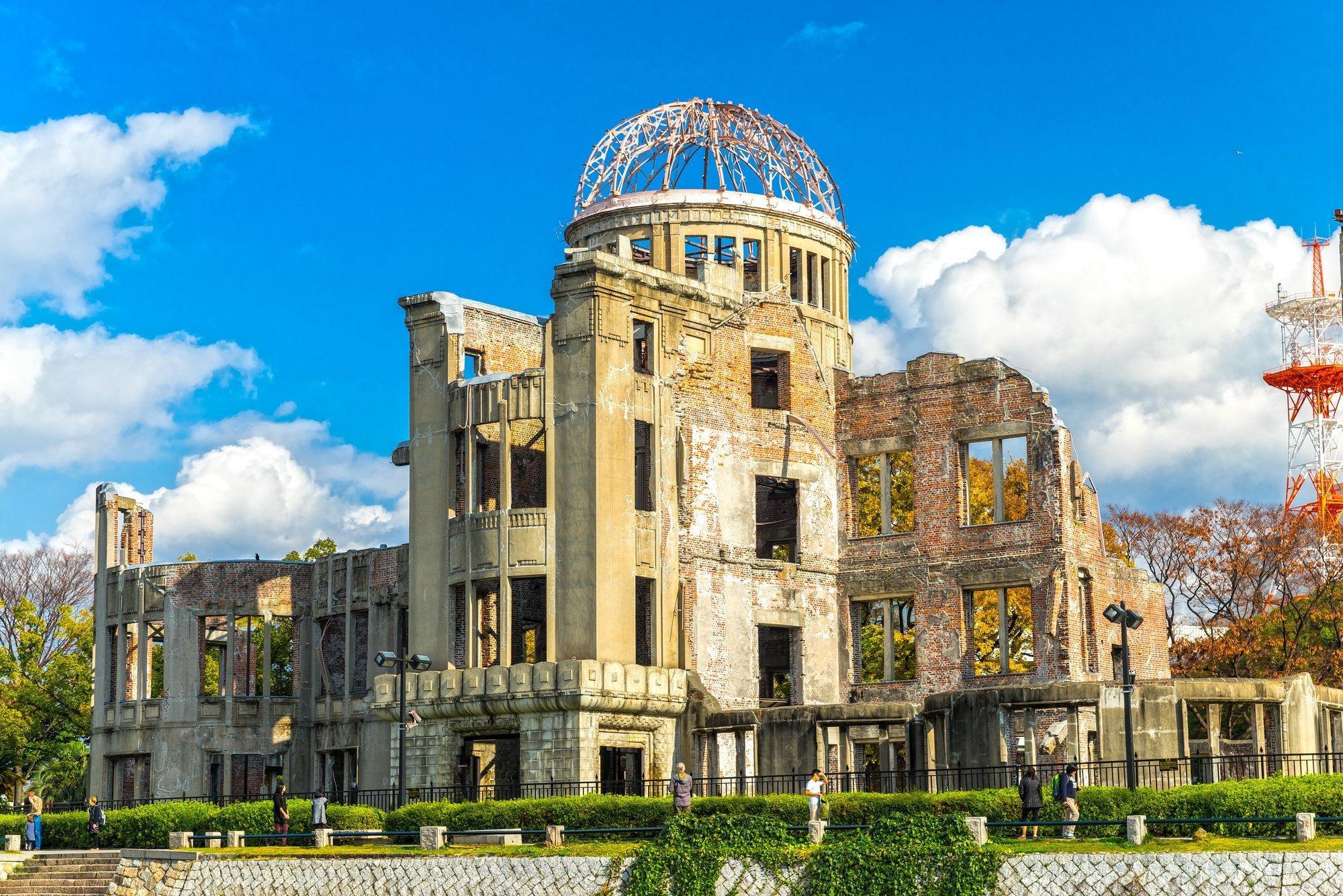 Das Bild zeigt das Friedensdenkmal von Hiroshima, ein von der Atombombe zerstörtes Gebäude mit einem Eisengerippe als Dach im Zentrum der Stadt.