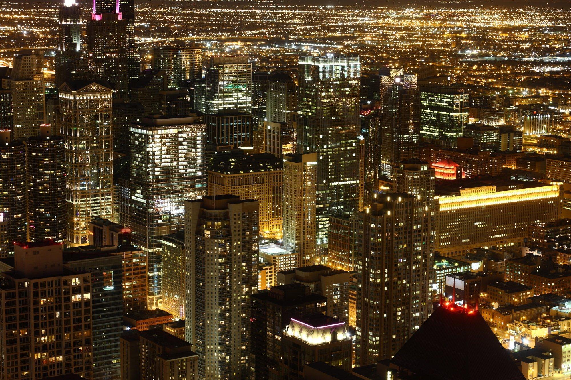 Das Bild zeigt die Innenstadt von Chicago mit zahlreichen Wolkenkratzern und greller Beleuchtung bei Nacht.