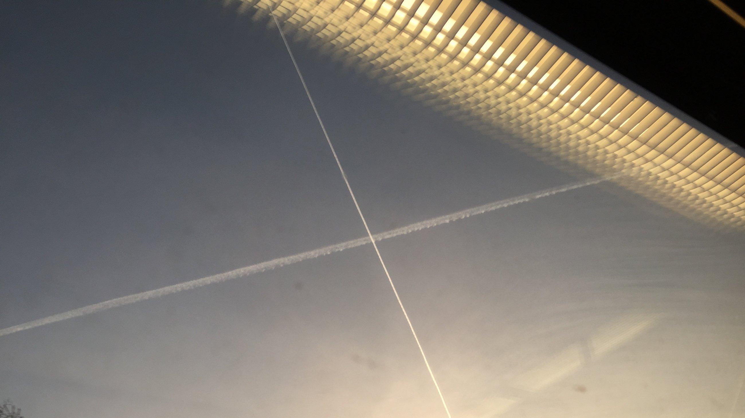 Kondensstreifen am Himmel durch ein Fenster fotografiert