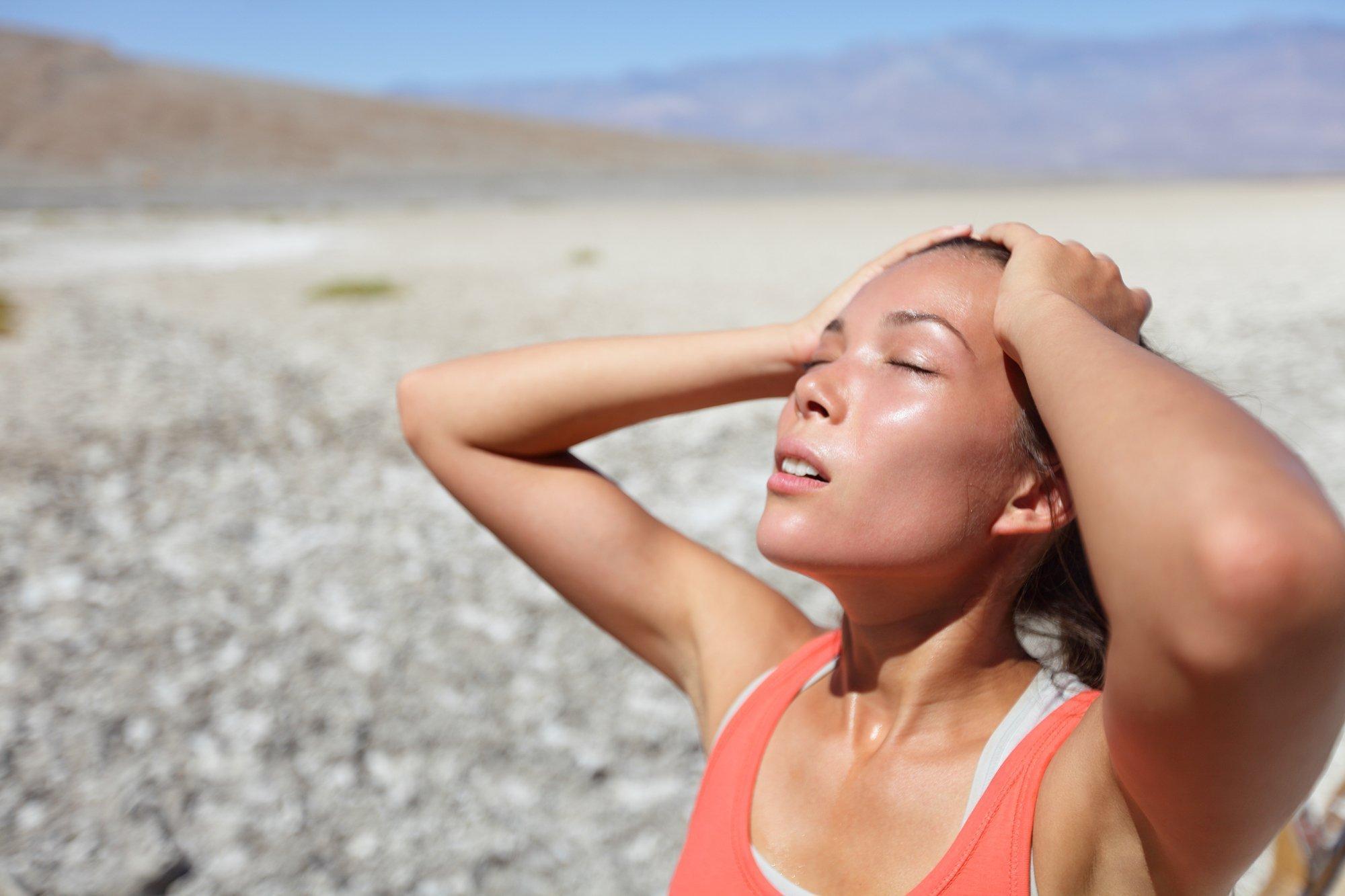 Das Bild zeigt eine Frau in der Wüste, sie sieht durstig aus.