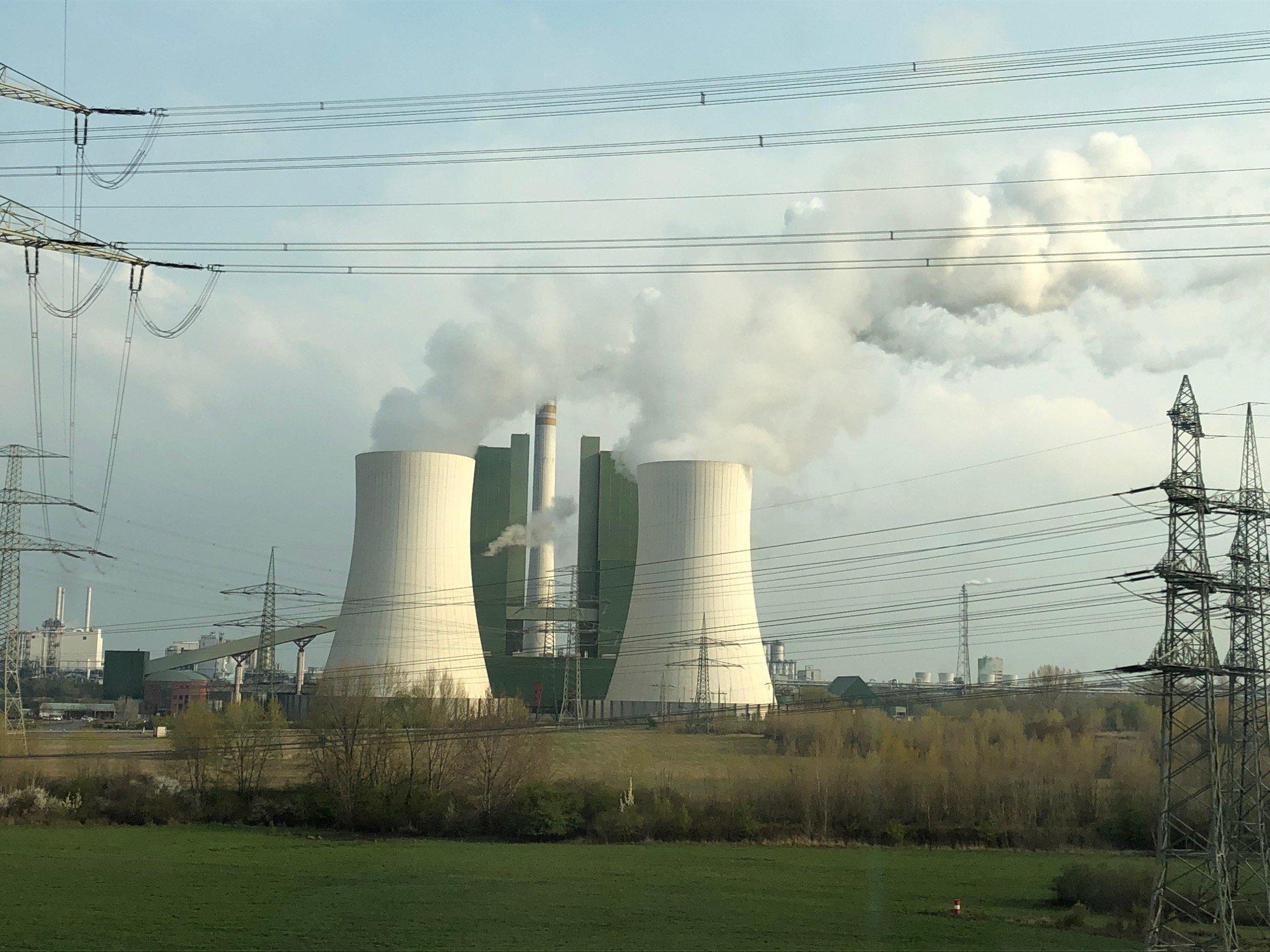 Ein Braunkohlekraftwerk. Aus den Schornsteinen strömt Rauch.