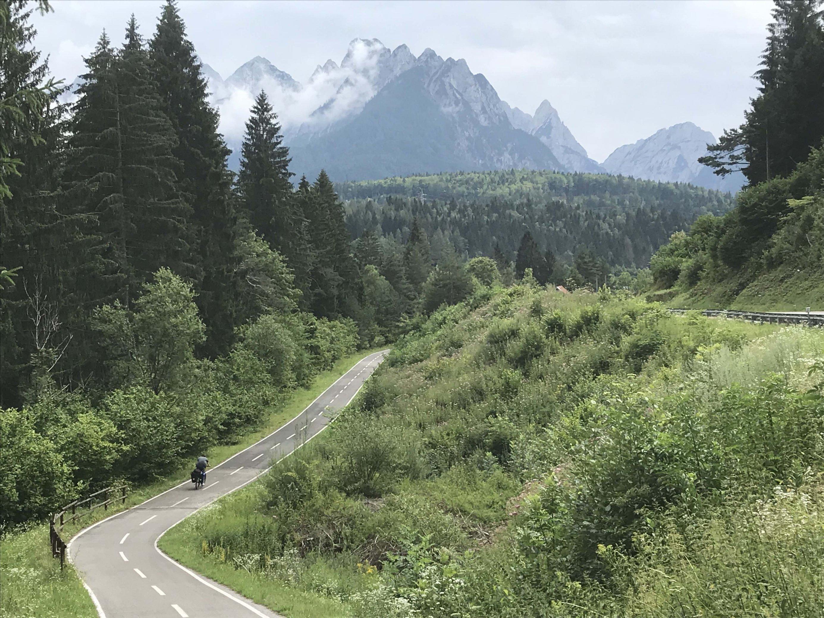 Aufnahme einer Talstraße. Im Hintergrund sieht man ein Gebirge.