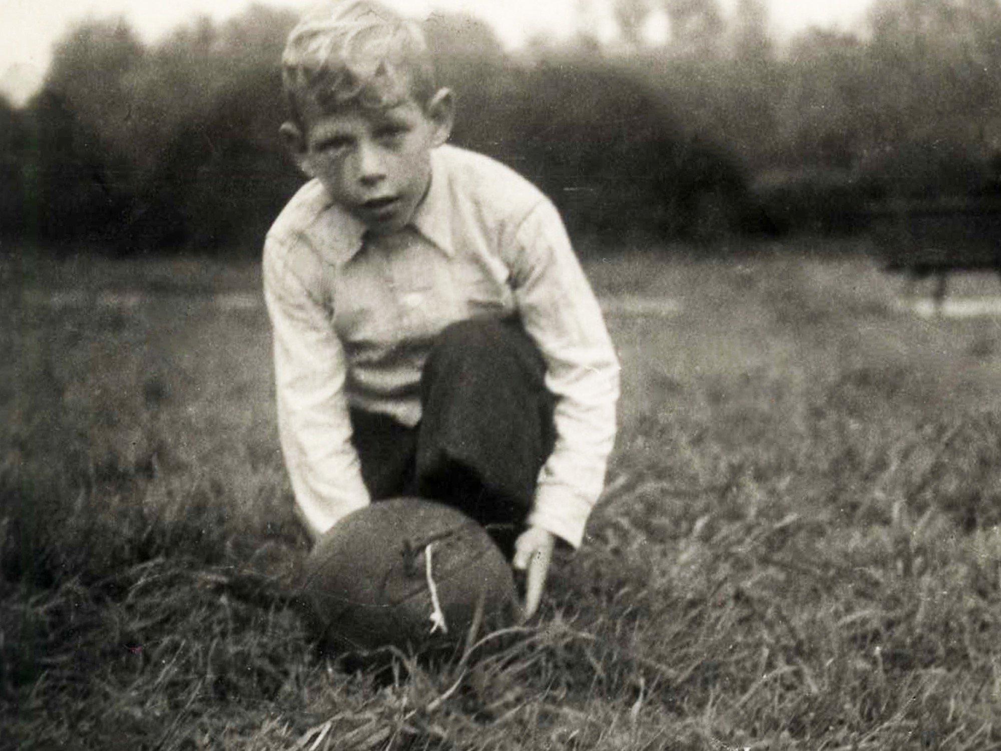 Kinderfoto von Paul Crutzen. Er kniet auf der Wiese. Vor ihm liegt ein Fußball.