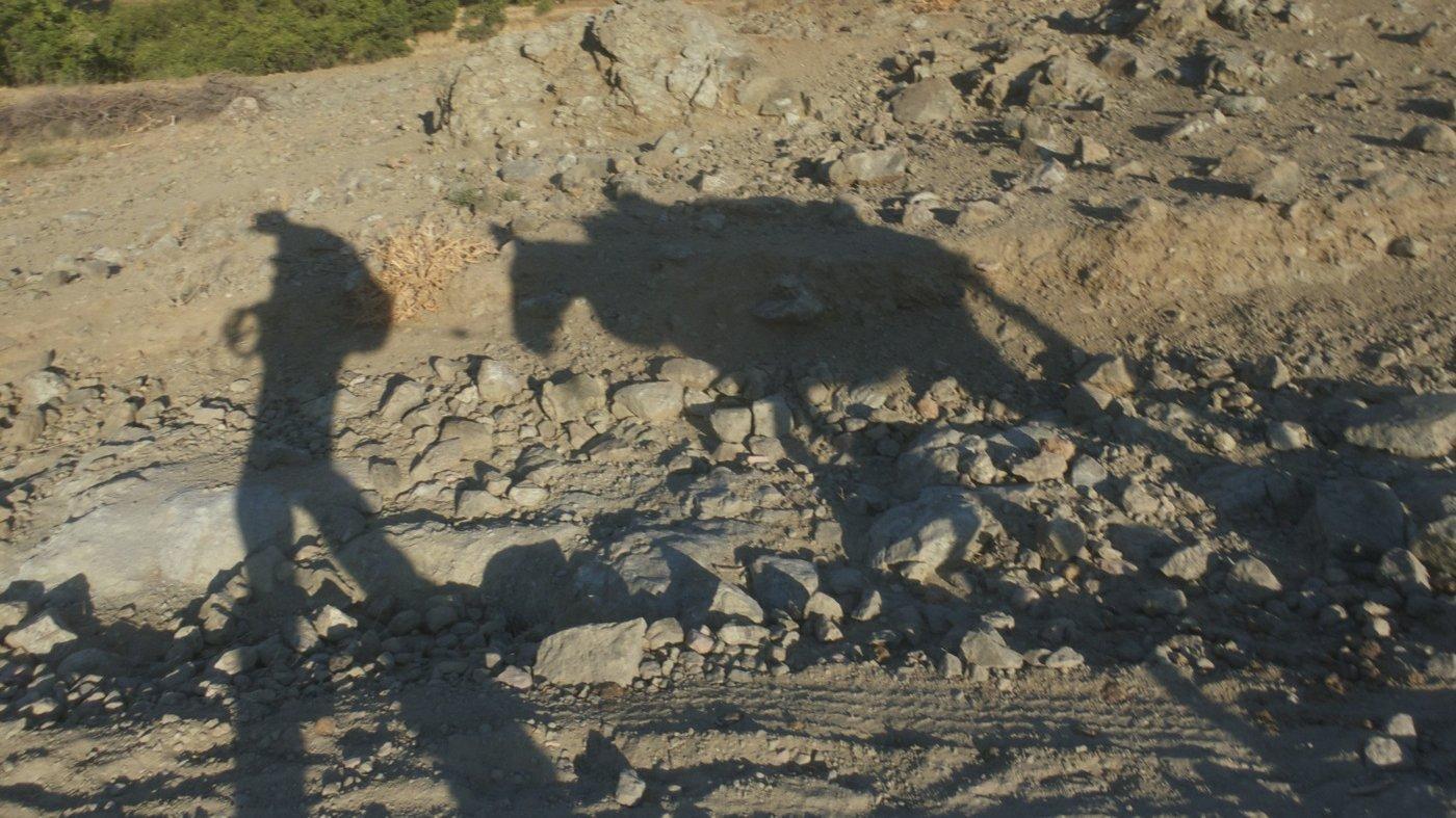 Der Schatten eines Mannes und eines Pferdes / Esels auf steinigem Boden.