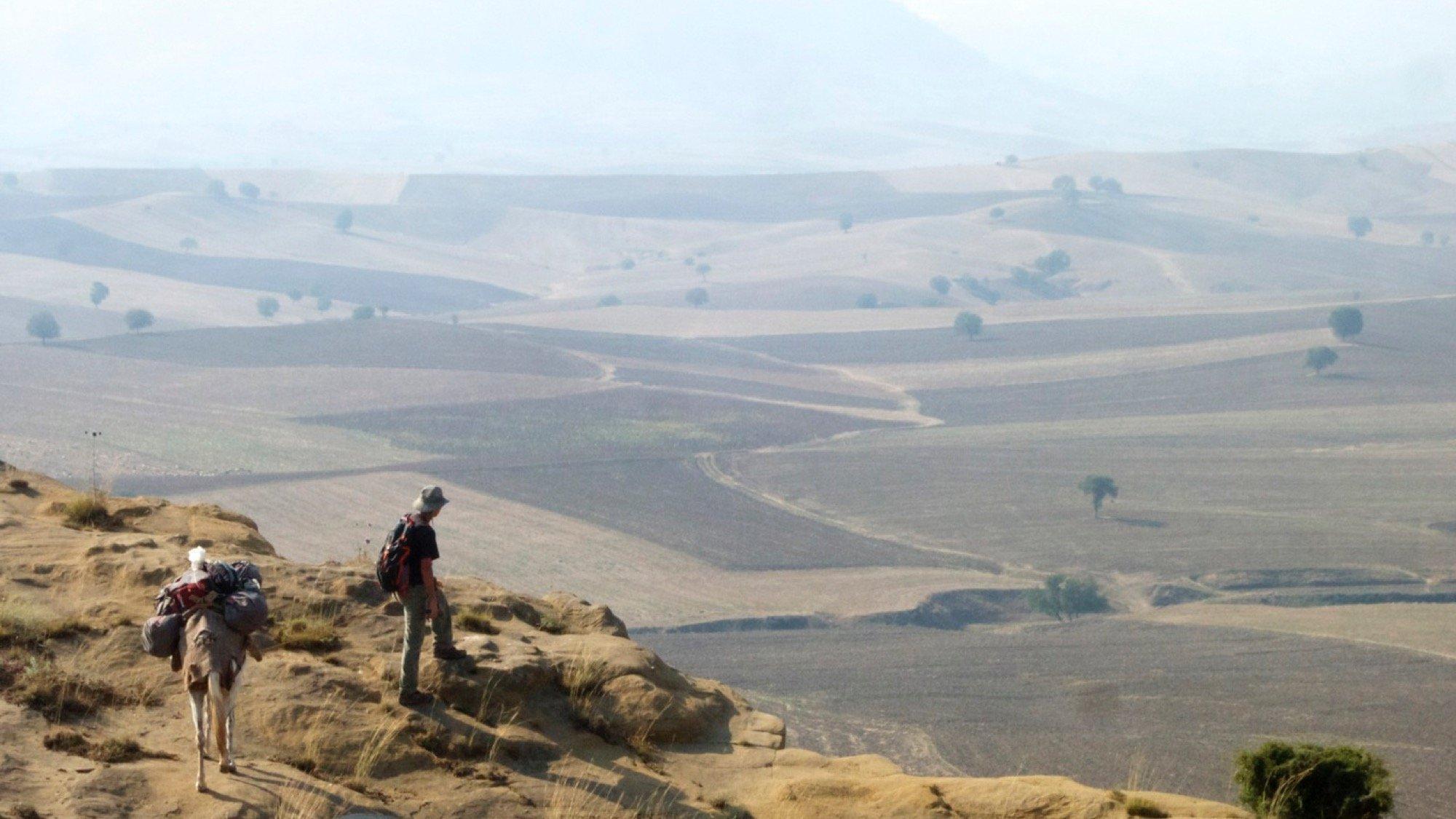 Der Journalist Paul Salopek steht am Rand eines Berges und schaut in die Ferne. Dort sind viele Felder zu erkennen.
