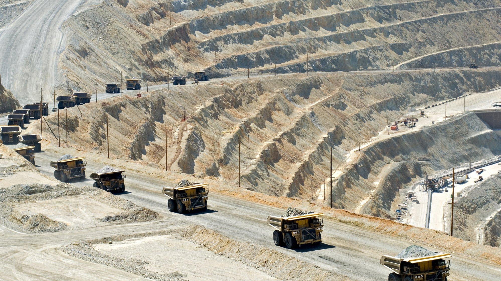 Das Bild zeigt eine Tagebaugrube, aus der eine Straße herausführt. Auf dieser Straße fahren in einer langen Kette Lastwagen, die Material abtransportieren. Das Bild symbolisiert Umwelteingriffe des Menschen.