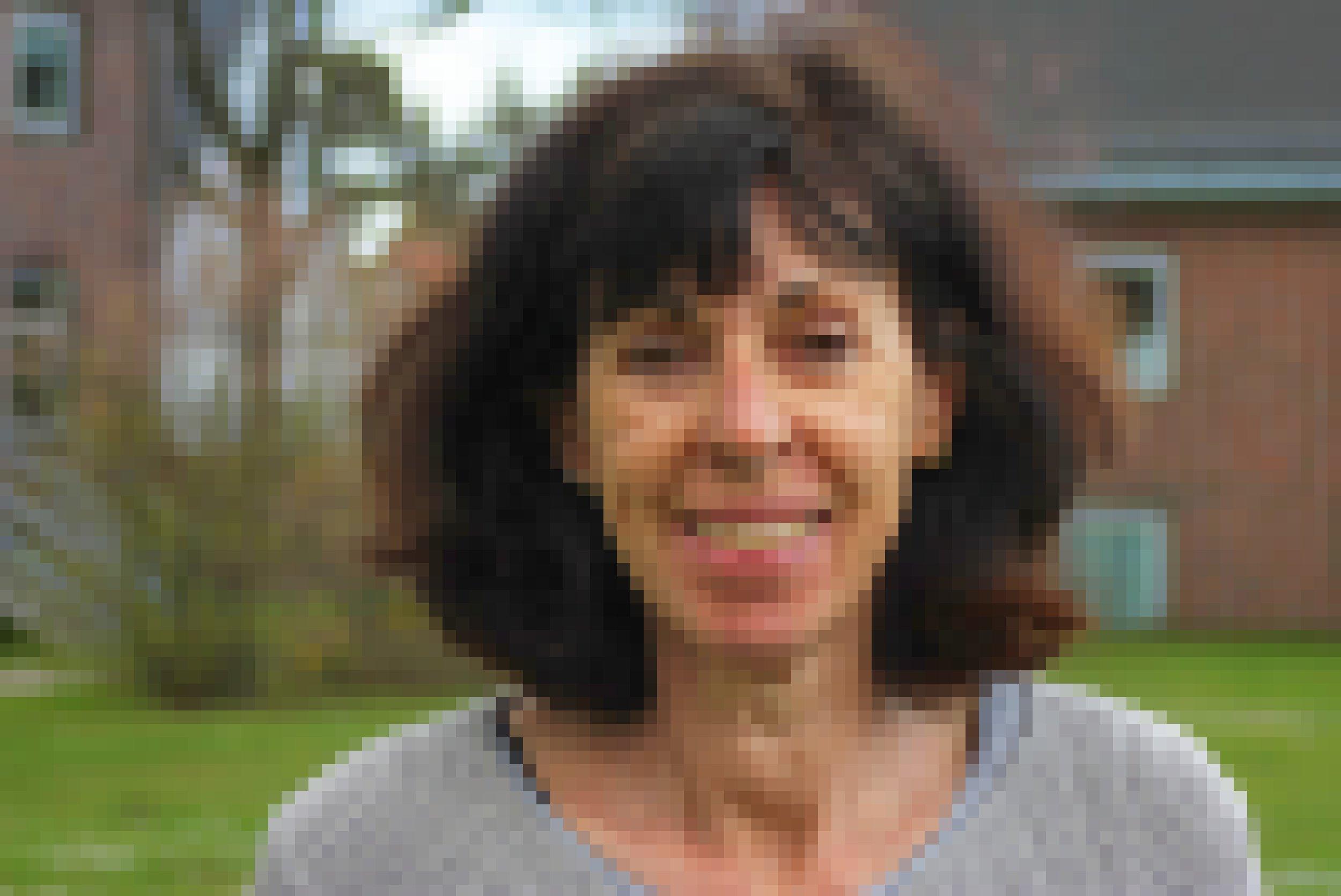 Eine Frau mit schulterlangem, leicht gewelltem braunen Haar lächelt in die Kamera.