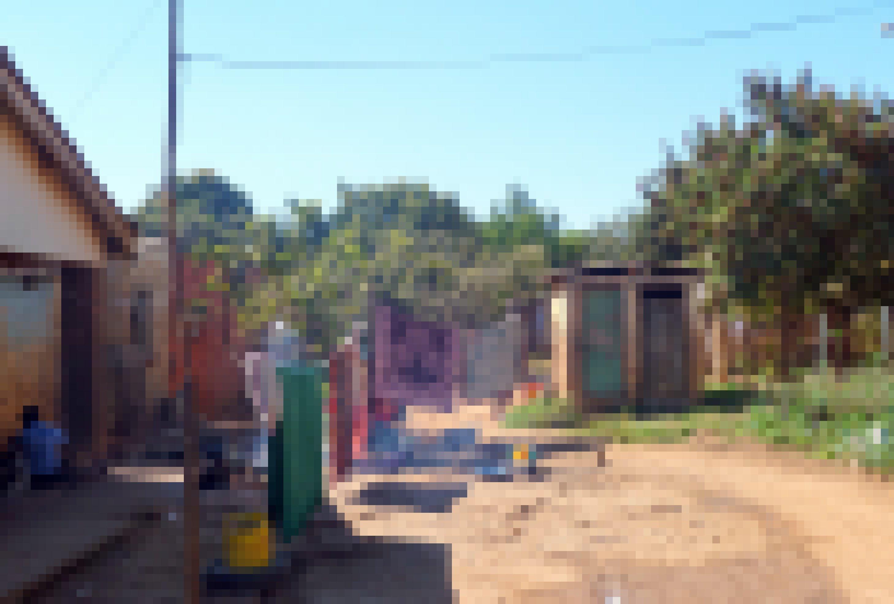 Das Bild zeigt ein kleines Haus mit Klohaeuschen und Waescheleine in einem Armenviertel in Simbabwe. Die Armut ist unuebersehbar.