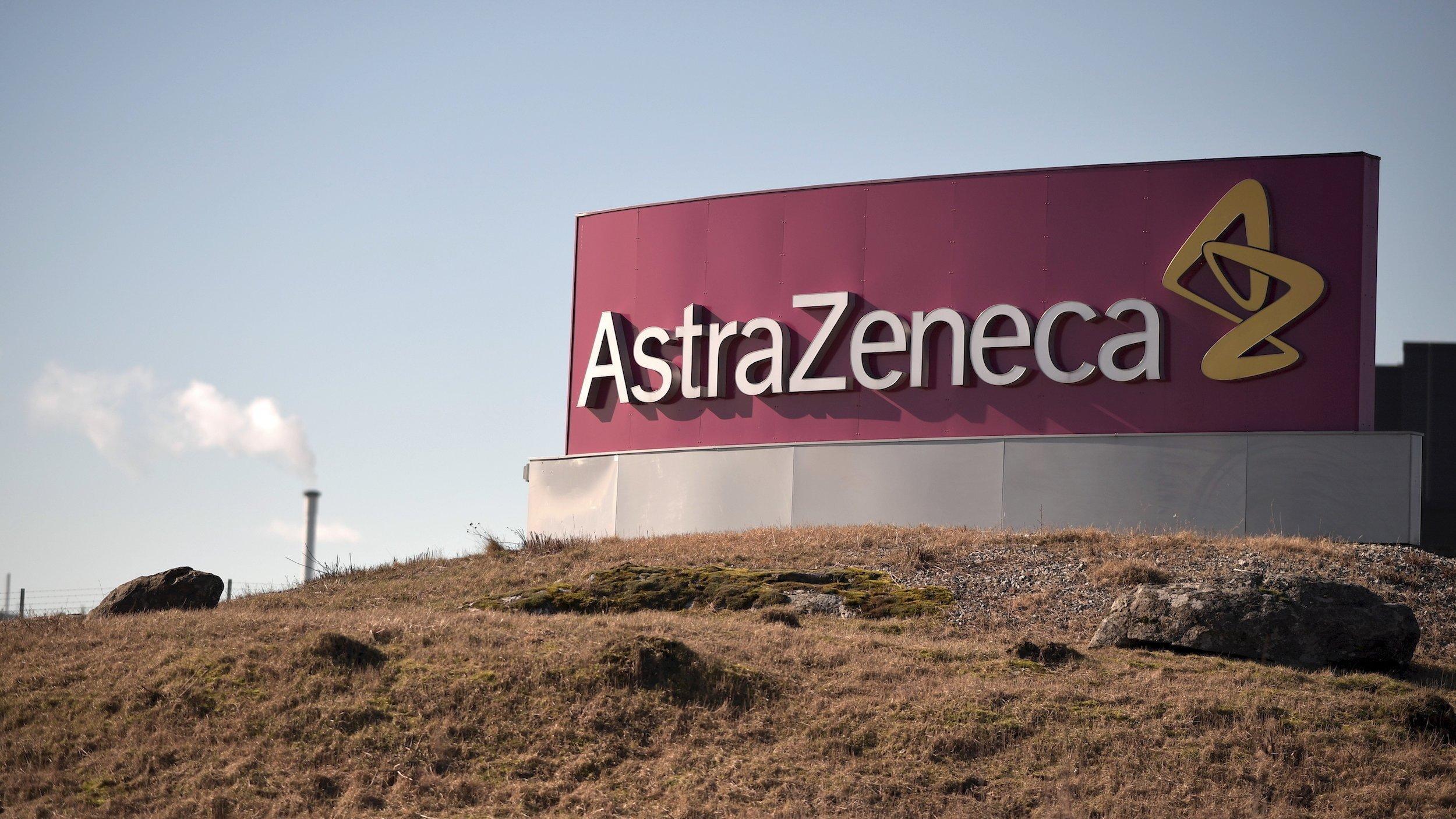 Das Logo von AstraZeneca vor einer Landschaft mit brauner Erde.