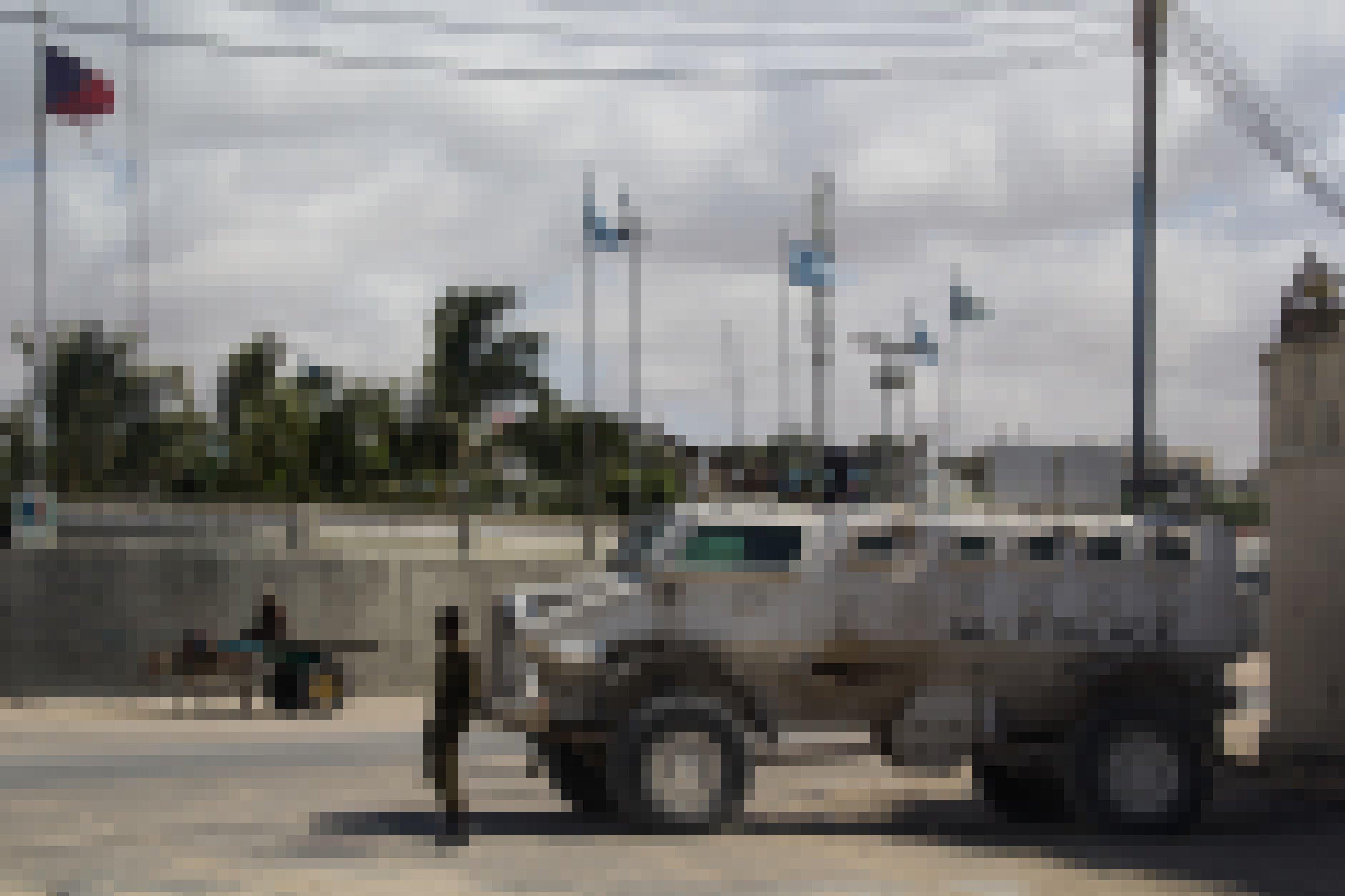 Ein weißer Panzer mit der schwarzen Aufschrift AU auf einem Platz in Mogadishu. Ein Mensch mit Eselskarren fährt vorbei, außerdem steht ein Soldat schräg vor dem Panzer.