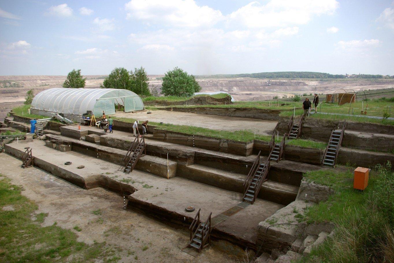 Das Foto zeigt die Grabung in Schöningen: Über mehrere Stufen sind die Erdschichten abgetragen, von Treppen verbunden. Hinten links ist eine Überdachung zu sehen und mehrere Wissenschaftler halten sich für Untersuchungen auf dem Gelände auf. Hier entdeckten sie im Jahr 2016den neuen, jetzt in einer Publikation vorgestellten Wurfstock.