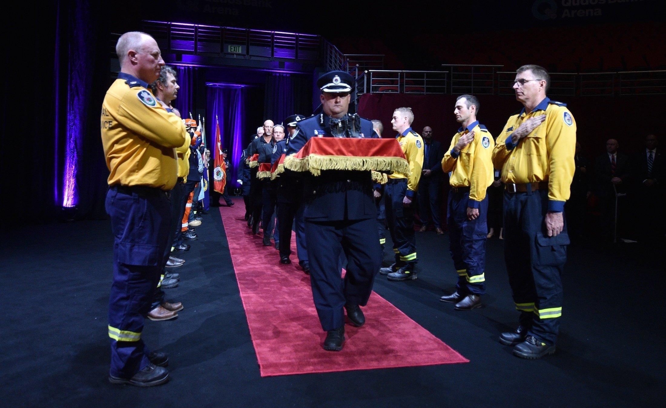 Feuerwehrmänner bilden in einer abgedunkelten Halle ein Spalier, während Kollegen in dekorierten Schachteln die Stiefel von Kameraden hereintragen, die bei den Bränden ums Leben gekommen sind,