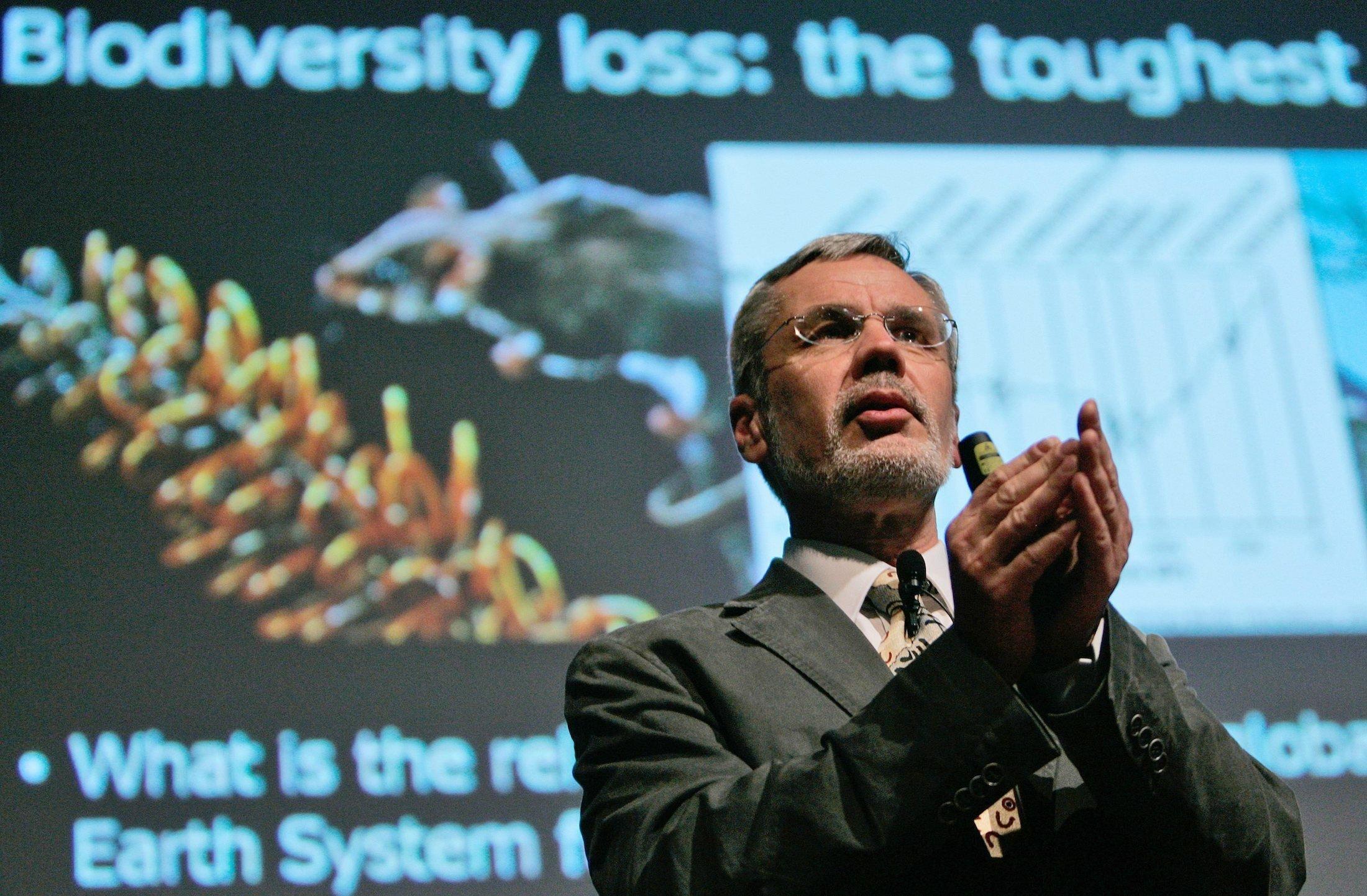 Steffen hat als Redner die Hände gefaltet. Hinter ihm ist eine projizierte Folie zu sehen, auf der das Wort Biodiversität steht.