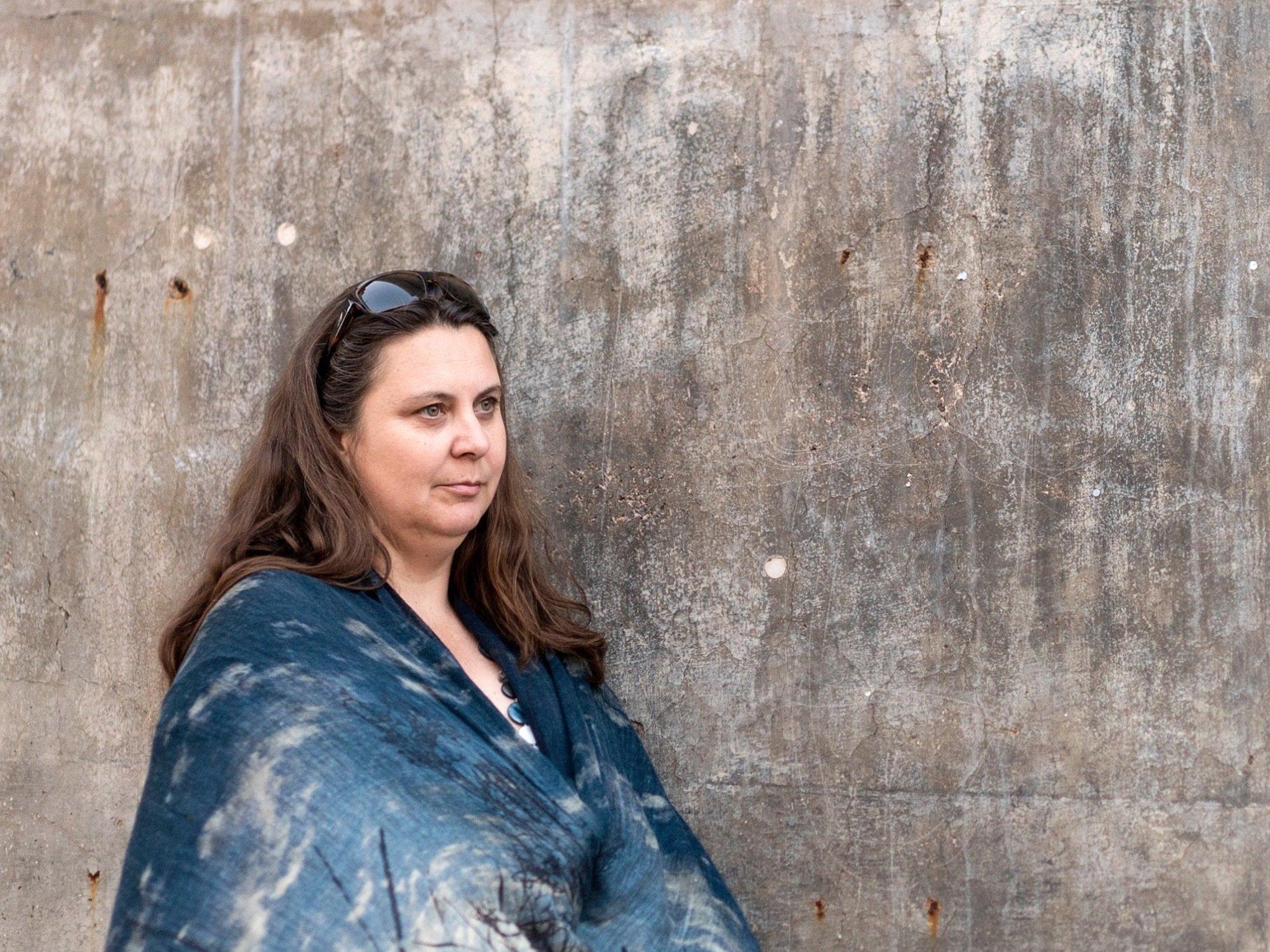Auf dem Bild steht die Klimaforscherin Nerilie Abram in ein schönes blaues Tuch gehüllt vor einer kahlen Betonwand. Sie schaut nachdenklich in die Ferne.