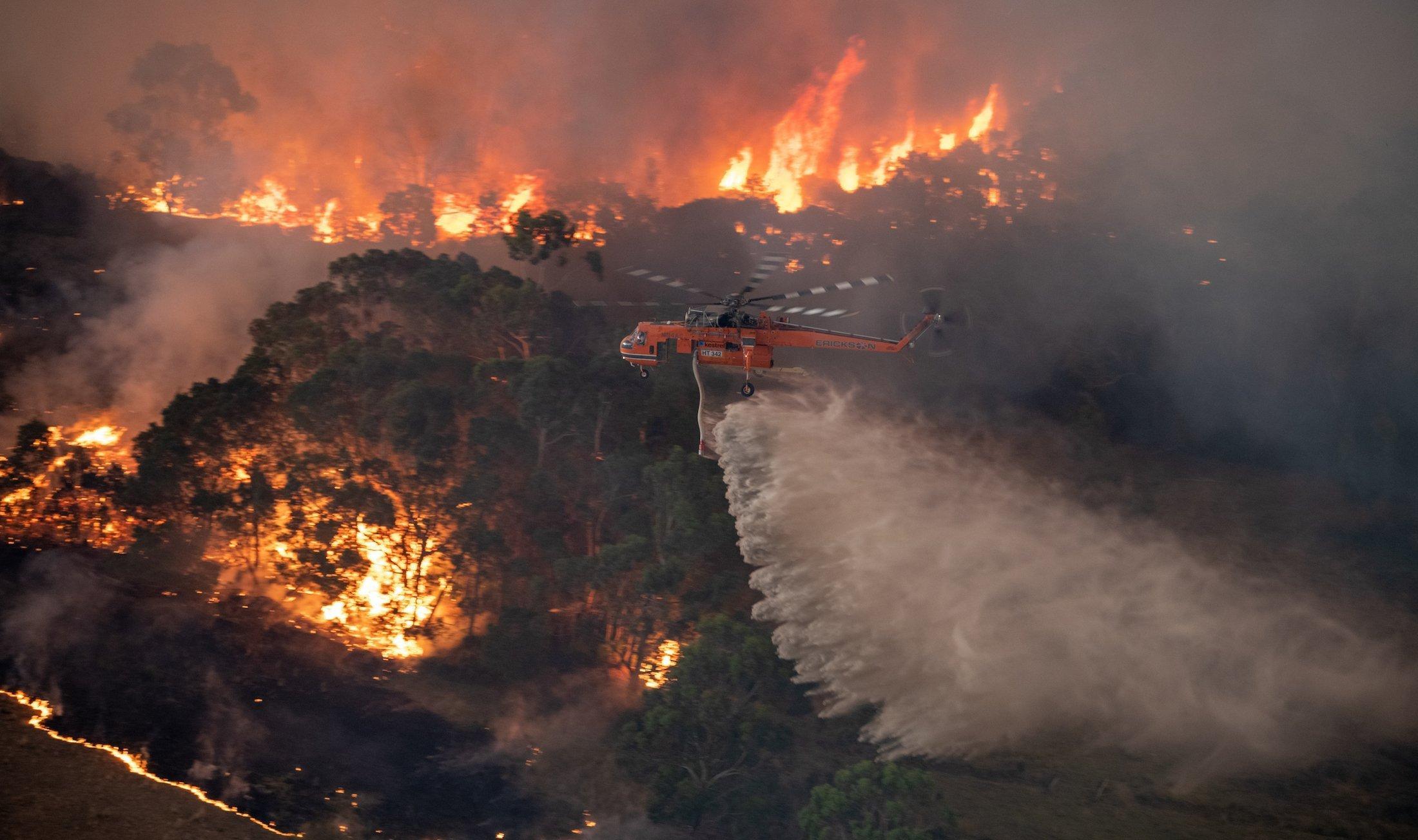 Das Bild zeigt, wie ein Feuerwehrhubschrauber bei Nacht eine große Menge Wasser über einem Waldbrand ausschüttet.