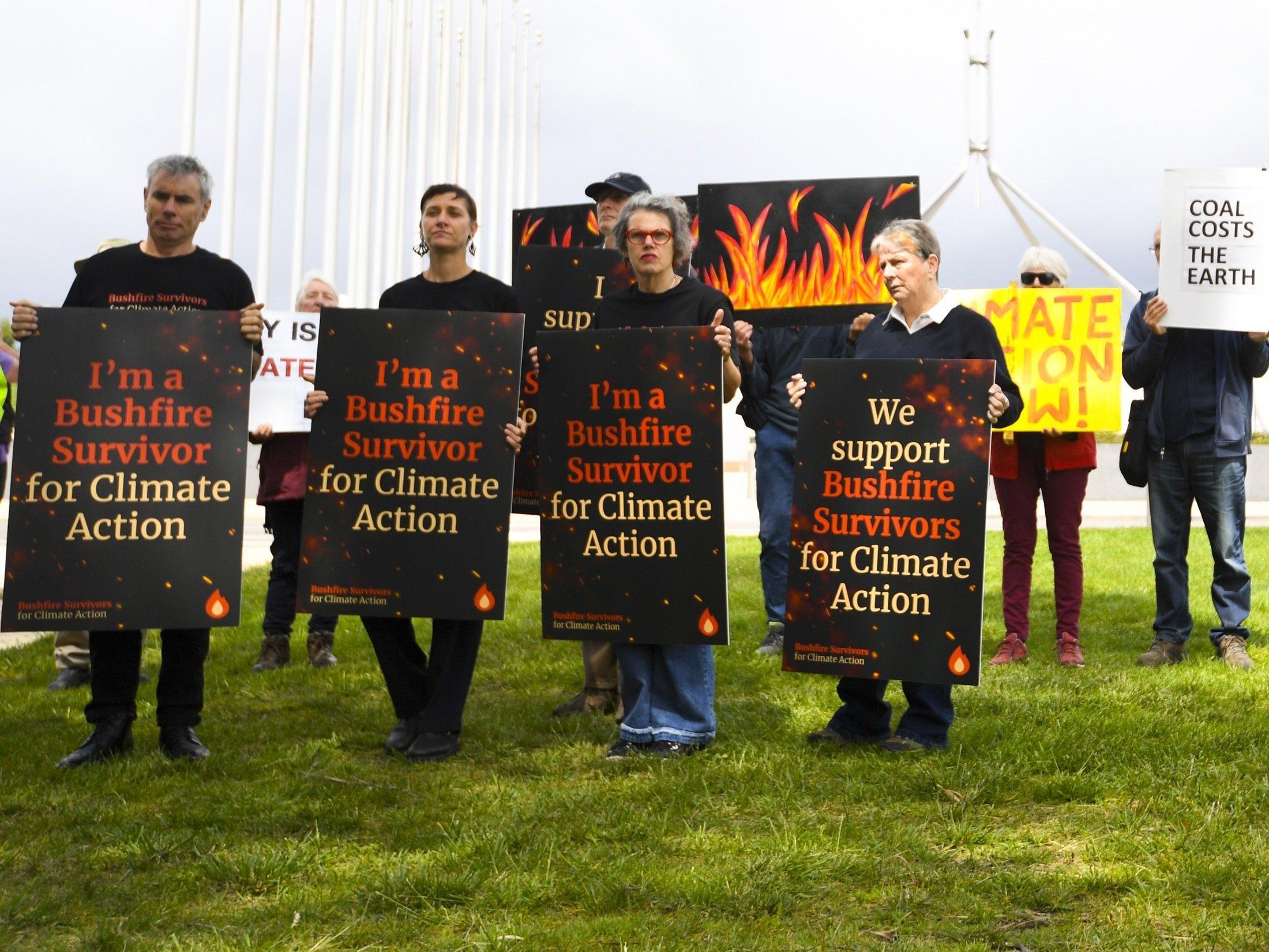 Demonstrantïnnen, die sich als Überlebende der Bushfire bezeichnen, fordern mit Schildern, dass die Regierung beim Klimaschutz endlich handelt.