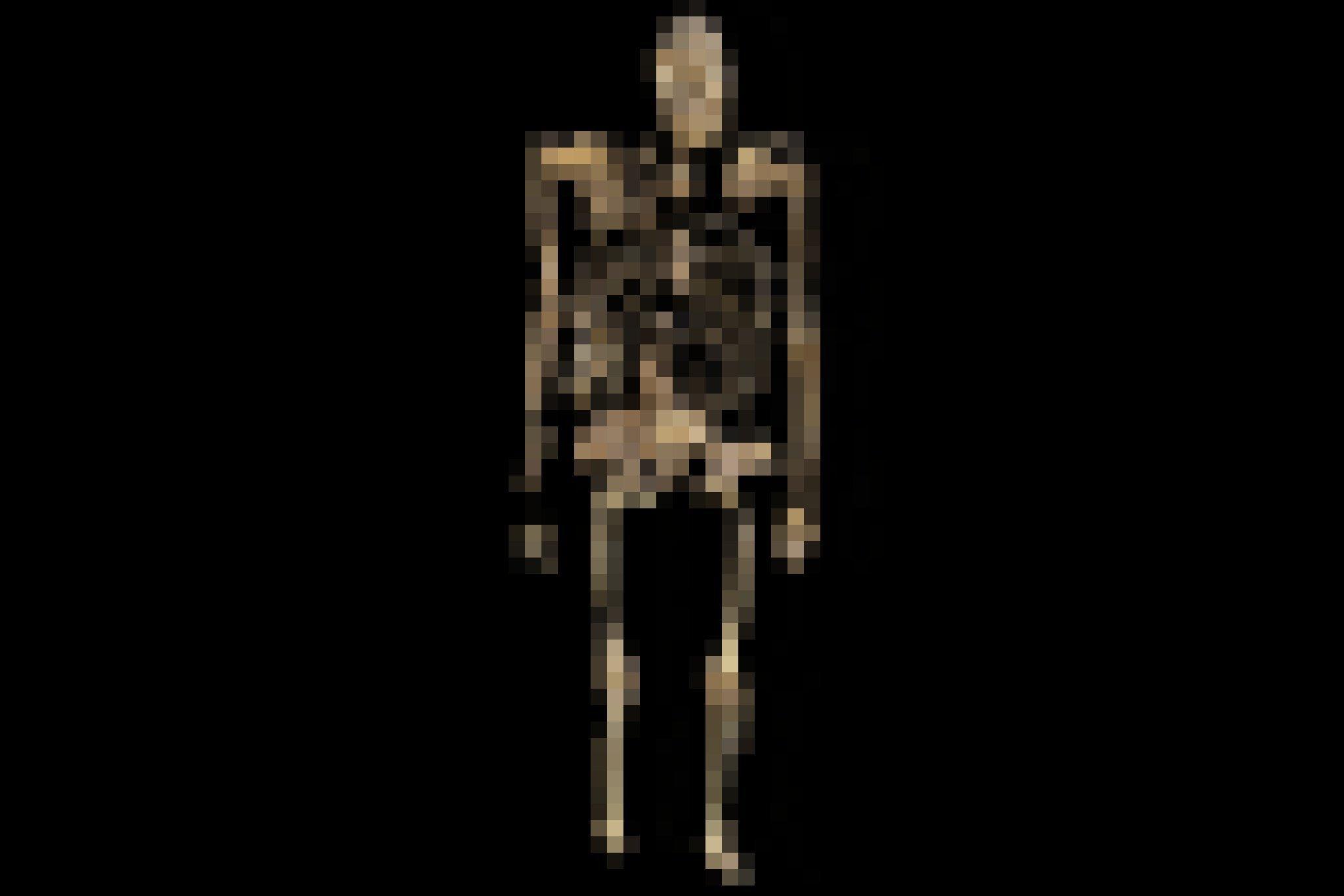 Vor schwarzem Hintergrund ist ein in aufrechter Position gezeigtes, weitgehend erhaltenes fossiles Skelett zu sehen, das wie eine Mischung zwischen Affe und Mensch wirkt.