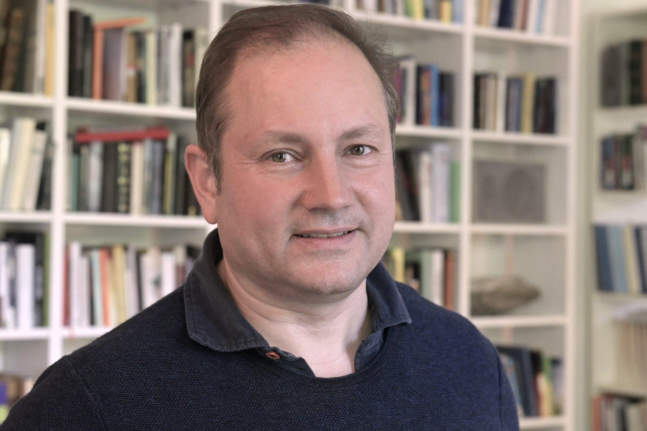 Der Journalist Christian Schwägerl vor einer Bücherwand.