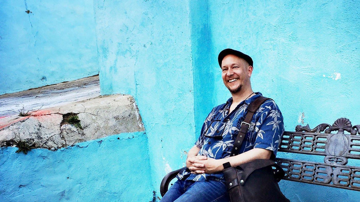 Der Autor und Fotograf Björn Göttlicher sitzt auf einer Bank vor einer blauen Wand