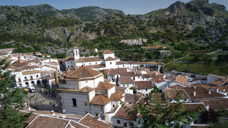 Ansammlung weißer Häuser mit roten Dächern inmitten einer bergigen, grün durchsetzten Mittelmeerlandschaft.
