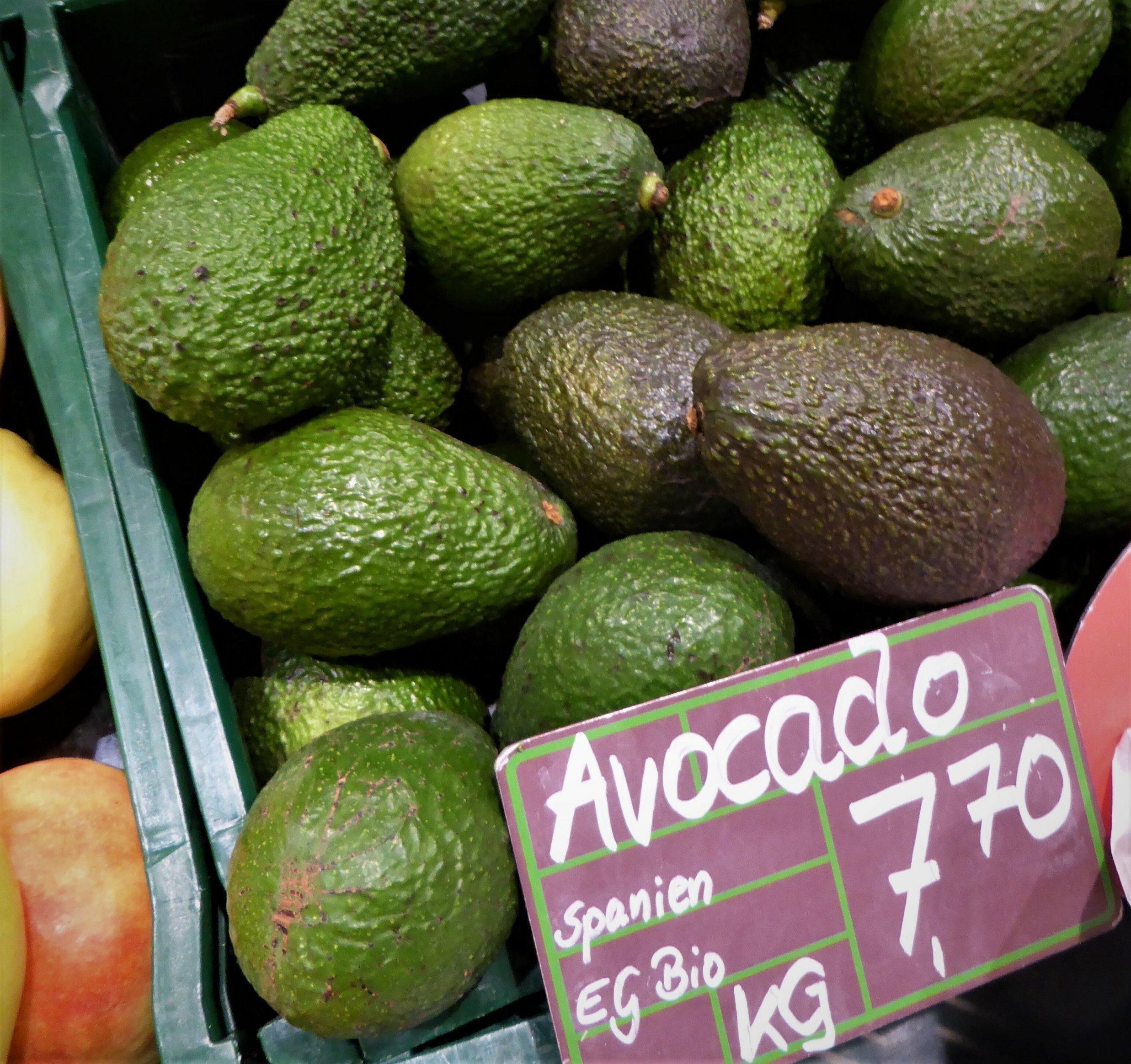 """Avocados in einer Plastikkiste mit der Preisauszeichnung """"Spanien EG Bio, Kilogramm 7,70Euro""""."""