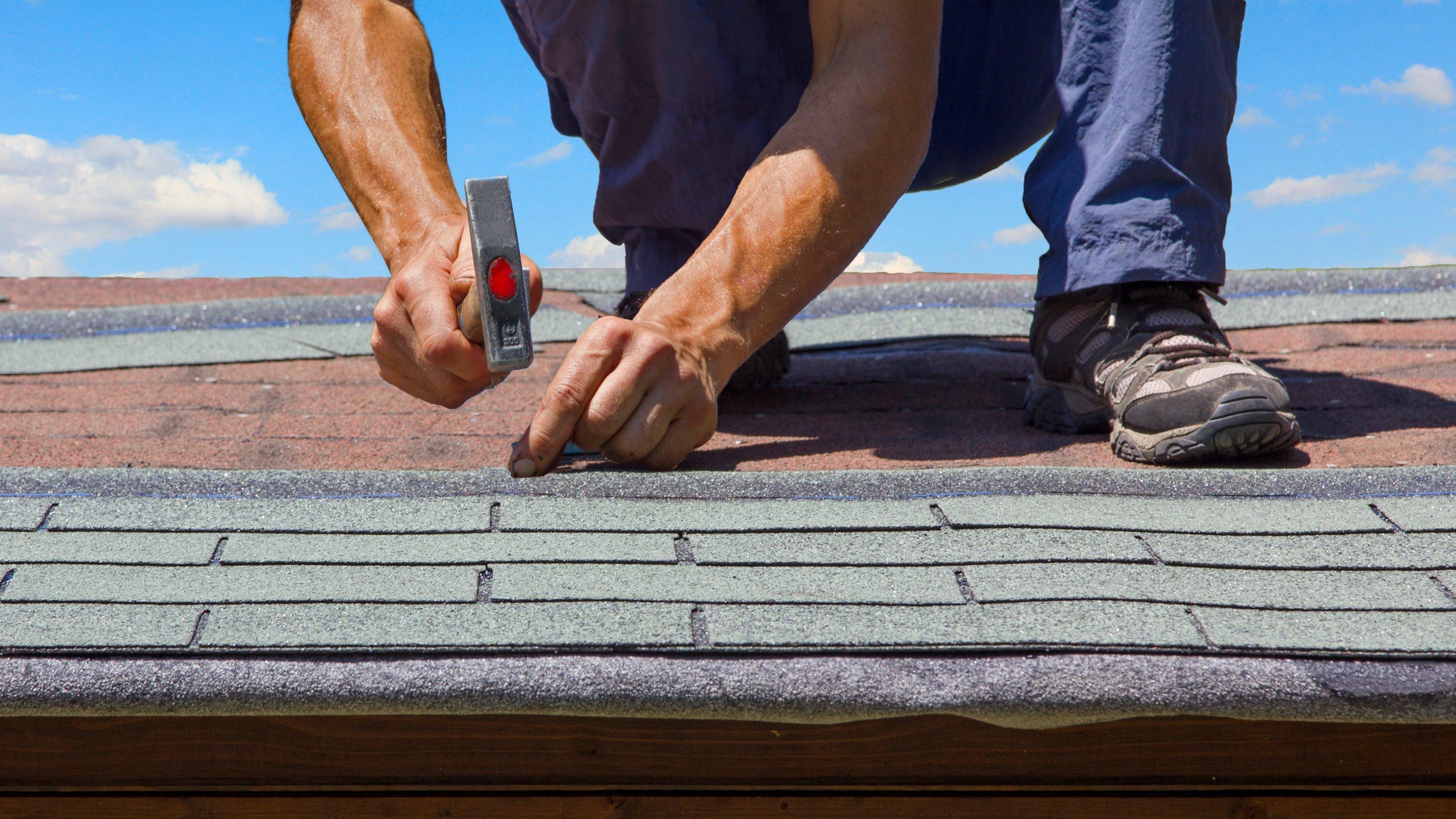 Ein Arbeiter, der nur knieabwärts zu sehen ist, hämmert eine Abdichtung auf ein Dach.