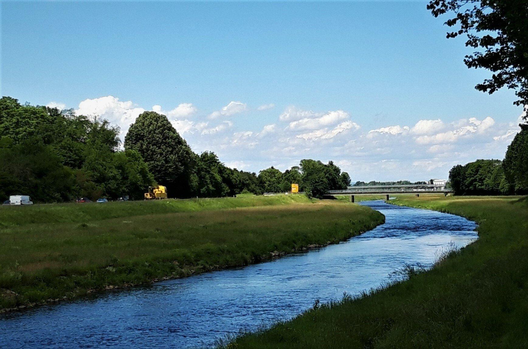 In fast giftig wirkendem Blau strahlt das Wasser der Murg normbreit zwischen den grünen Matten des zur Hochwasser-Bannung überbreiten, geradlinigen Flussbetts.