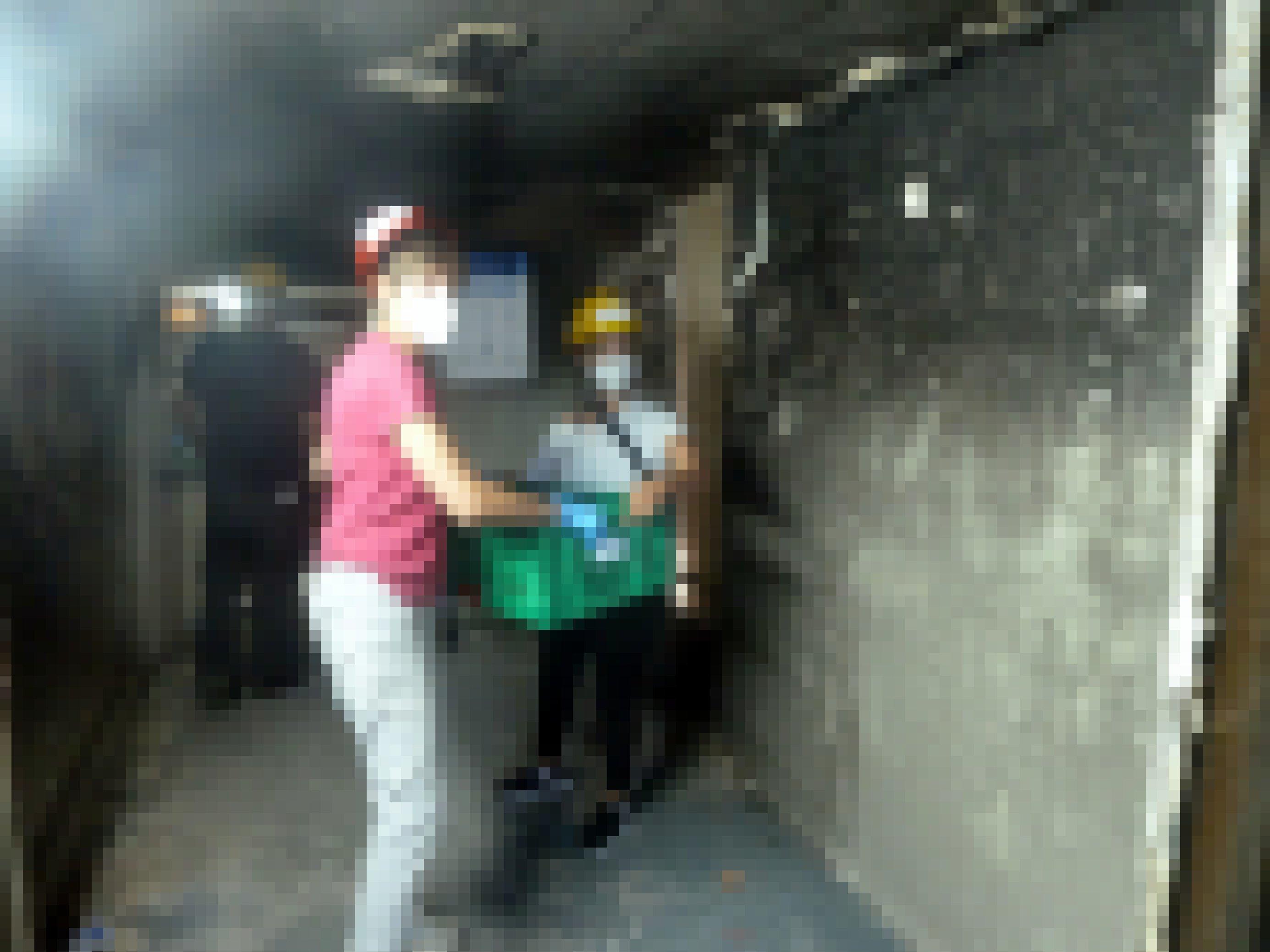 Eine Frau reicht einer anderen eine Kiste mit Archivmaterial, die Wände sind vom Feuer verrusst
