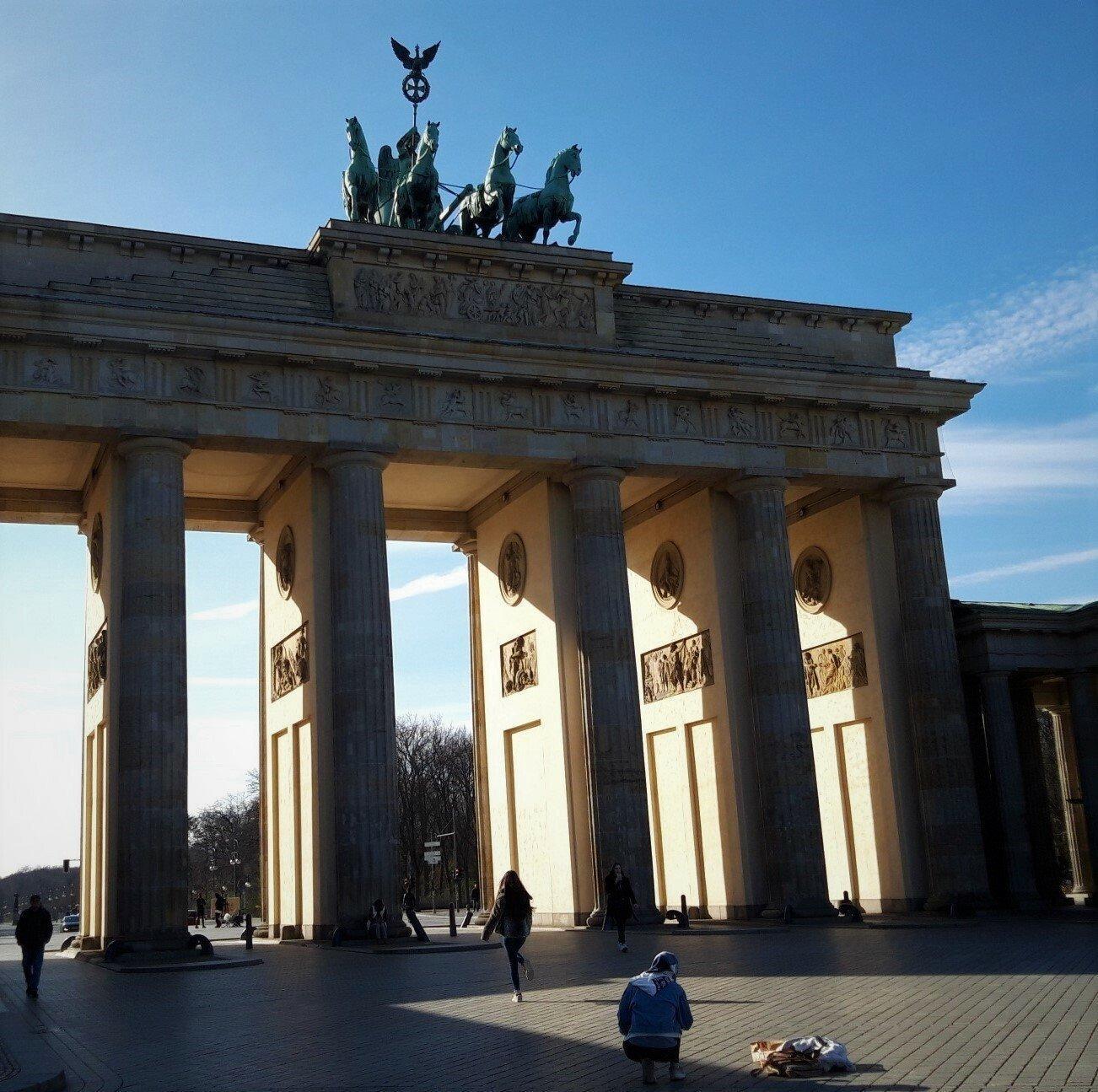 Seltene Leere vor dem Brandenburger Tor, durch das von Westen die Sonne scheint: Auf dem Vorplatz sind lediglich drei Passant·inn·en zu sehen.