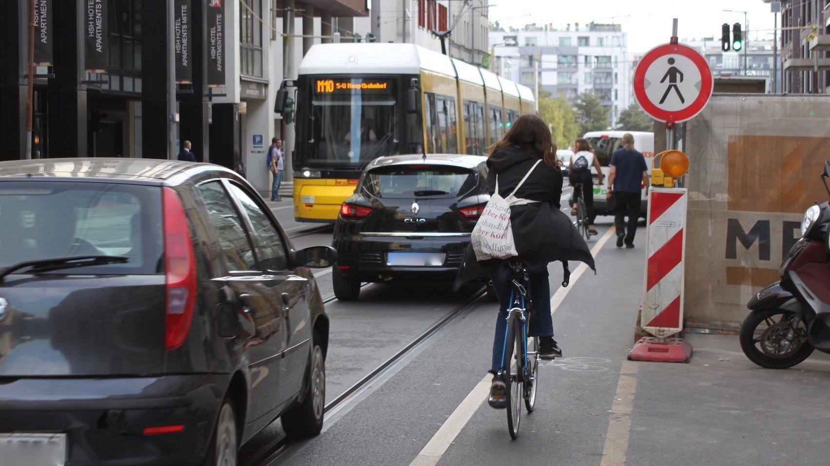 Eine befahrene Straße mit Baustelle. Ein Radfahrerin fährt an der Absperrung vorbei.