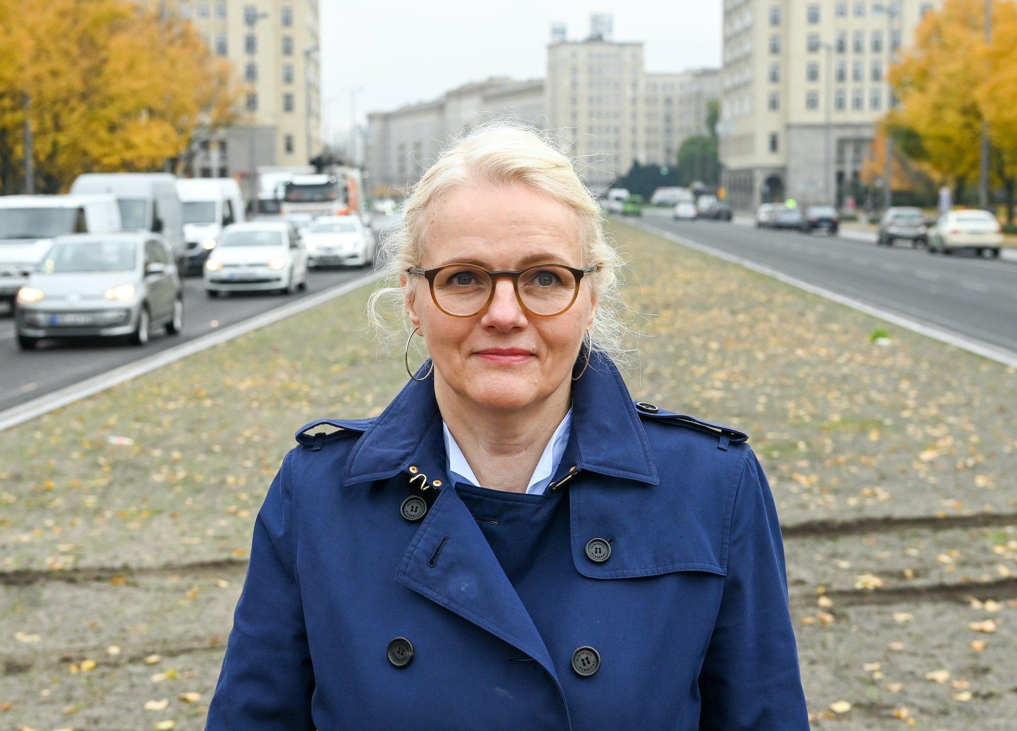 Regine Günther hat ihre blonden Haare zusammengebunden. Sie trägt eine dunkle Brille und einen dunkelblauen Trenchcoat. Sie steht auf einem breiten unbepflanzten Mittelstreifen einer viel befahrenen Straße