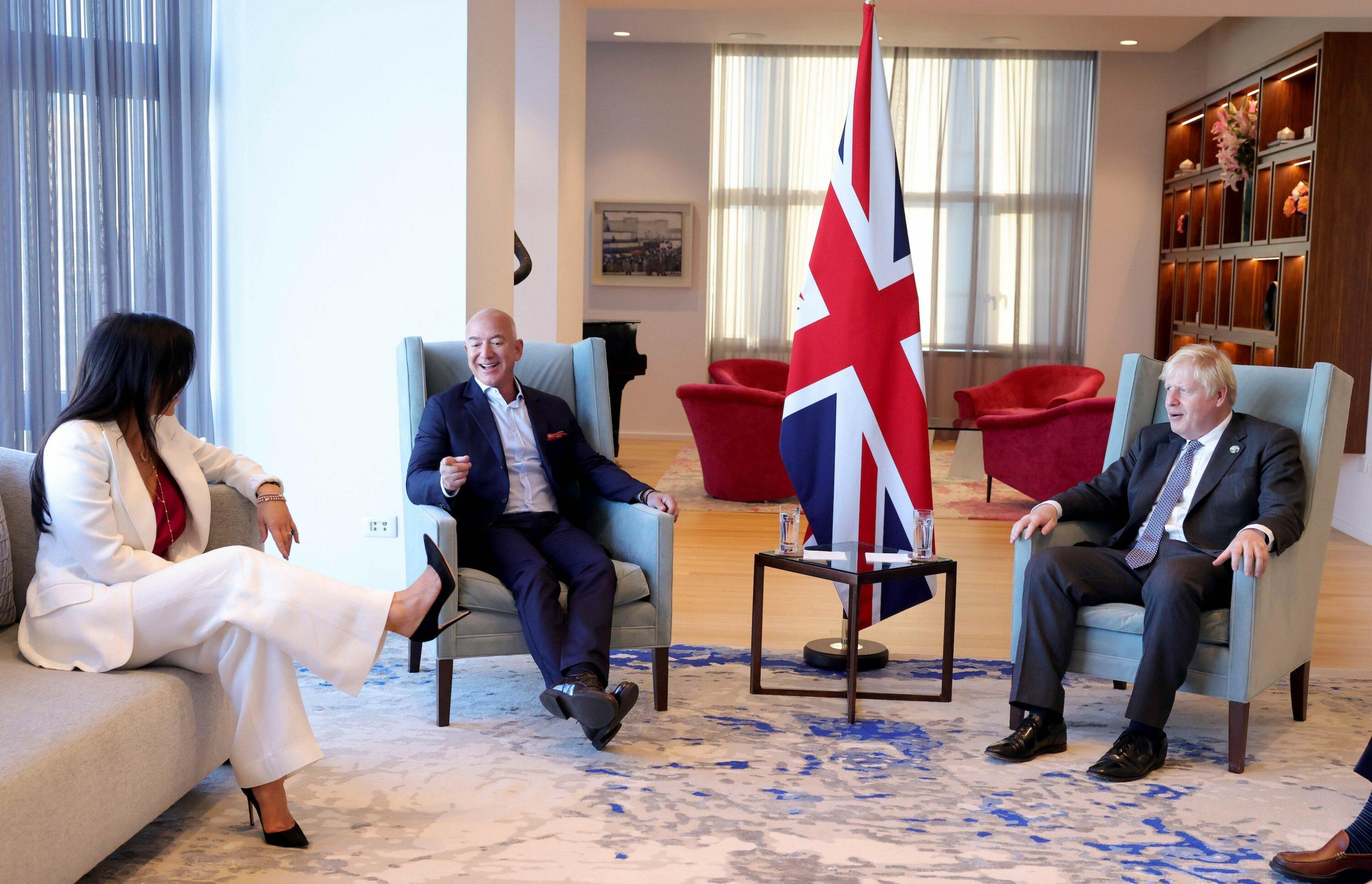 Bezos, Johnson und Sanchez in feinem Ambiente in New York, alle sitzen, im Zentrum eine britische Flagge.