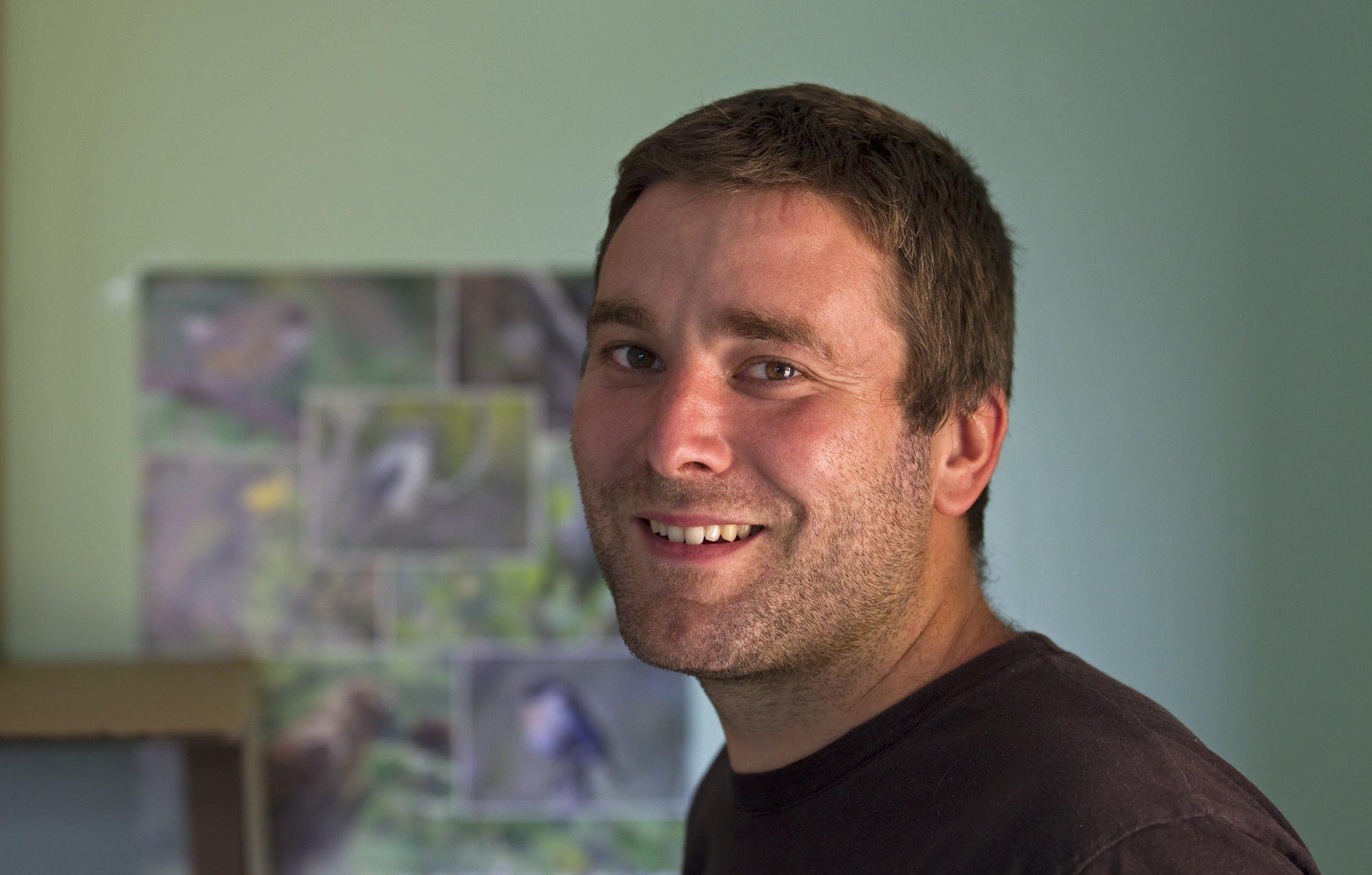 Damien Fouillot, der seit vielen Jahren den Schutz der letzten Newtonraupenfänger koordiniert, vor einem Plakat mit Fotos seiner Schützlinge.