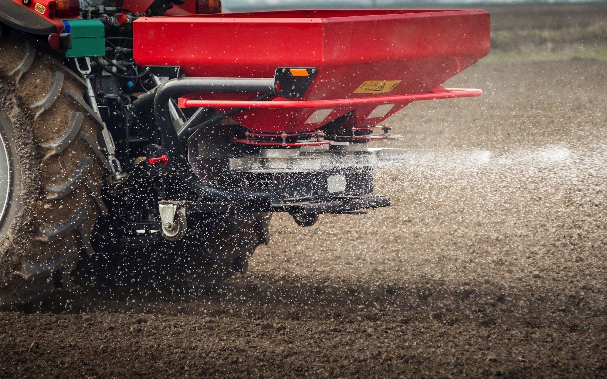Ein Traktor beim Ausstreuen von Dünger-Granulat.