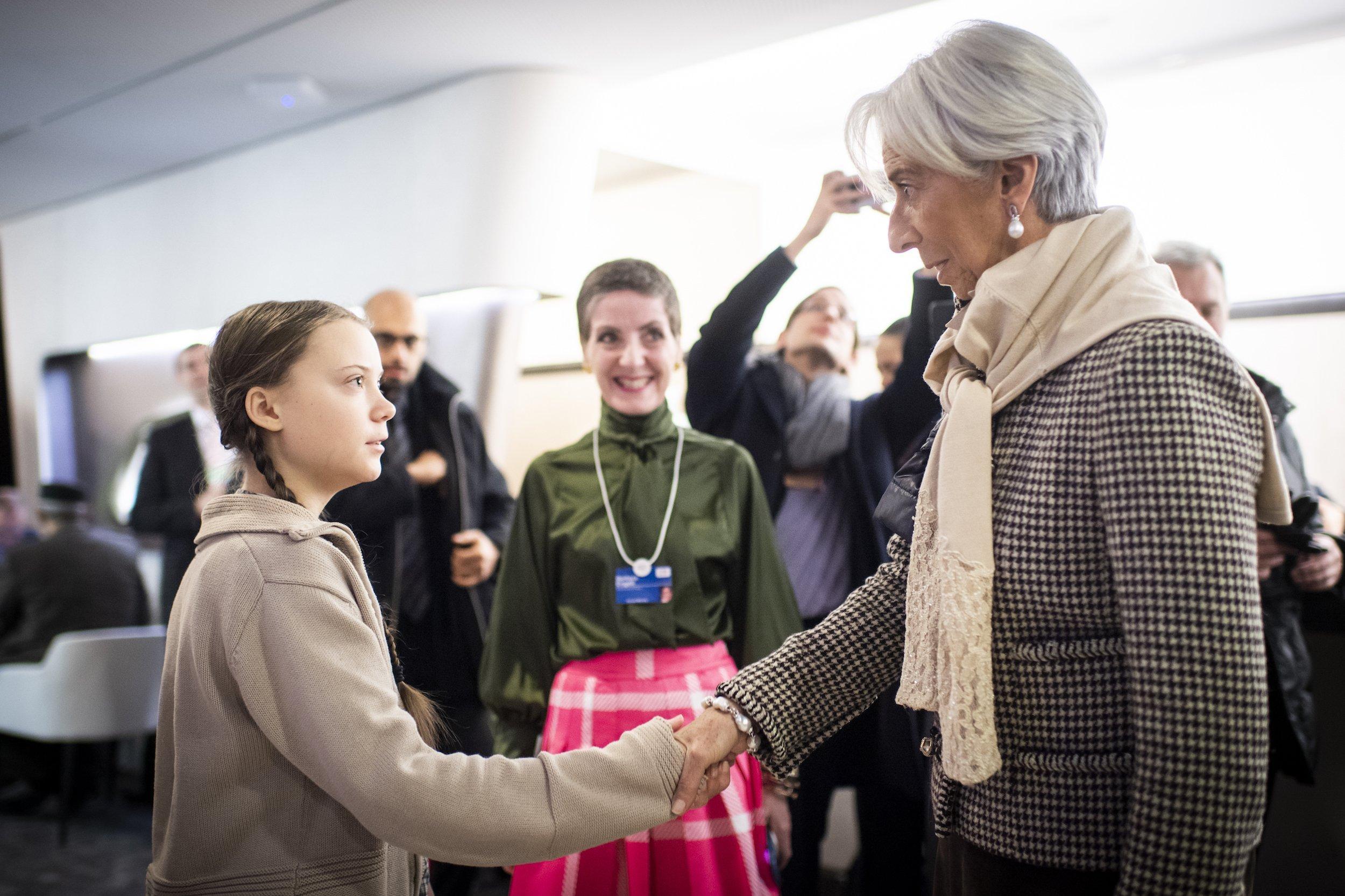 Greta Thunberg gibt der Chefin der Währungsfonds, Christine Lagarde, die Hand.