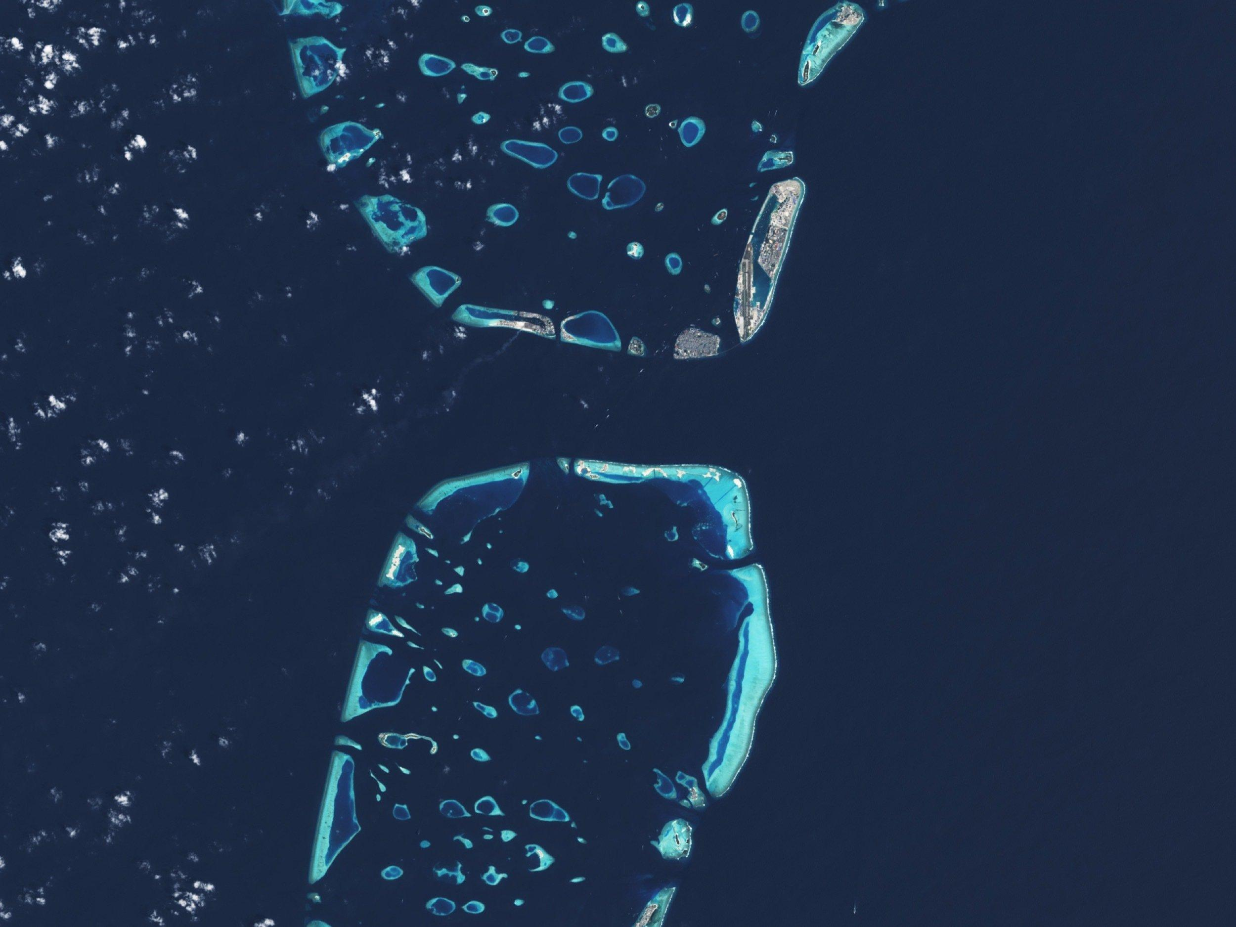 Satellitenaufnahme zeigt Koralleninseln im Indischen Ozean und die bebaute Hauptinsel der Malediven aus großer Höhe.