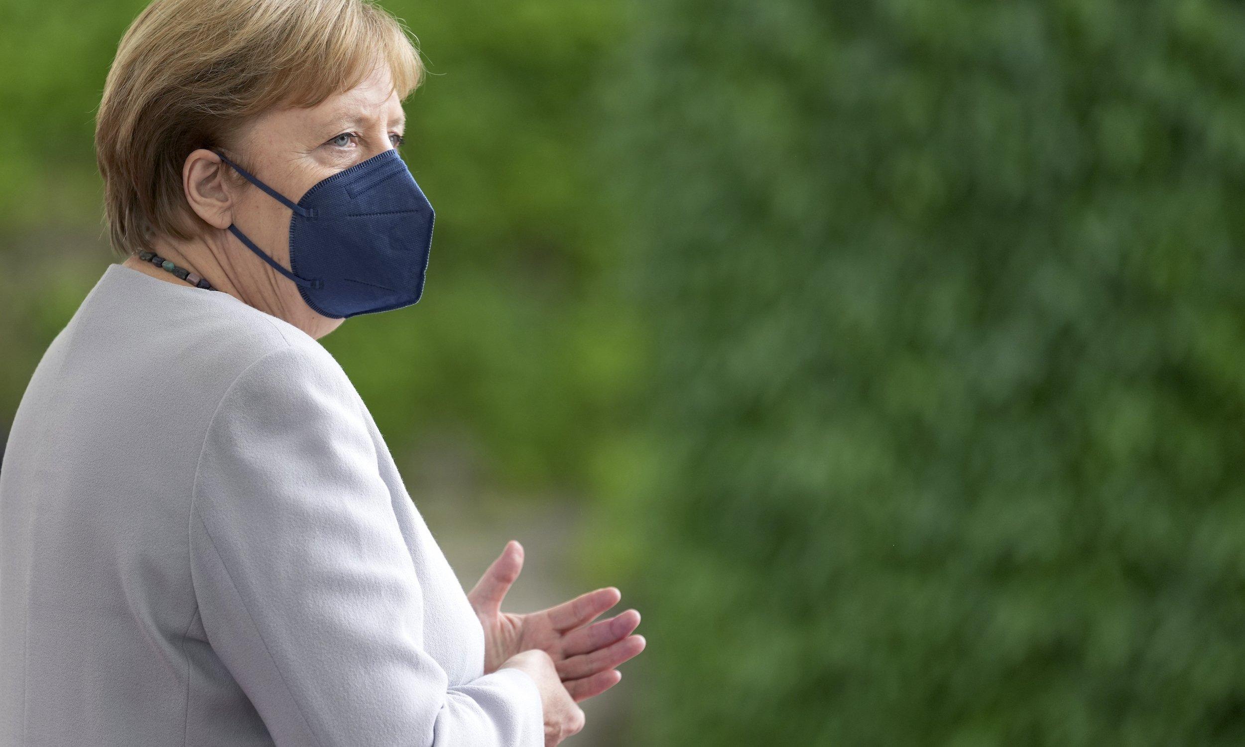Bundeskanzlerin Angela Merkel vor einer bewachsenen Wand, mit FFP2-Maske
