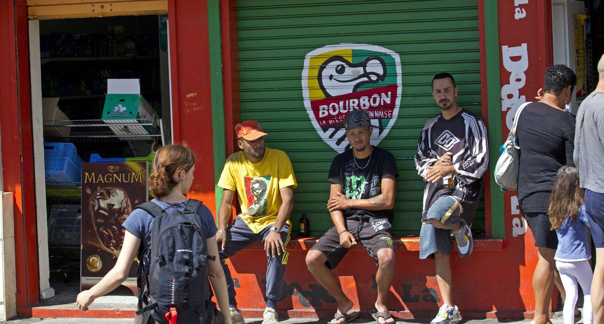 Eine Gruppe Jugendlicher sitzt und steht vor einem Kaffee