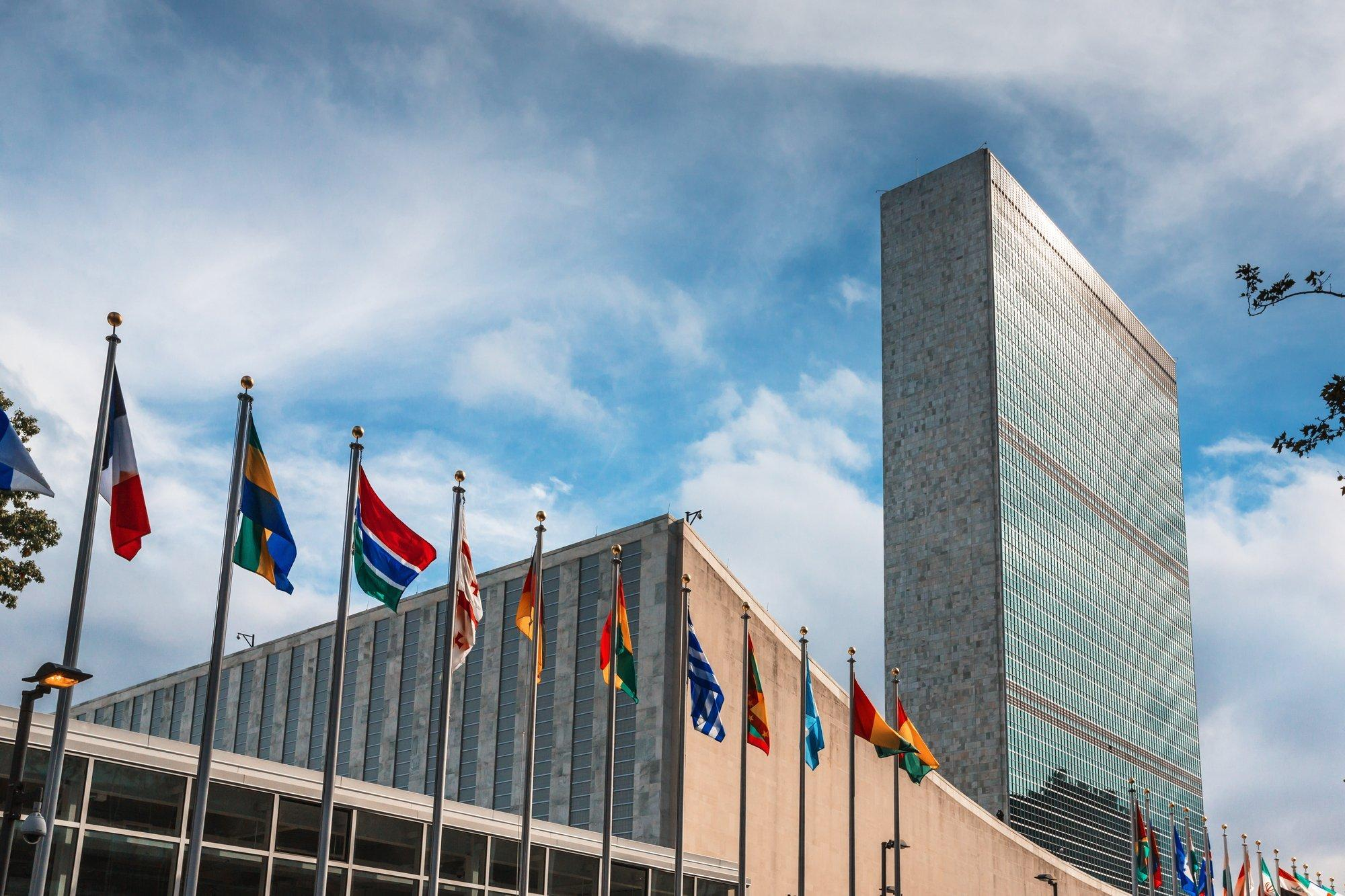 Außenaufnahme des Hochhauses der Vereinten Nationen in New York mit zahlreichen Flaggen von Mitgliedsstaaten.
