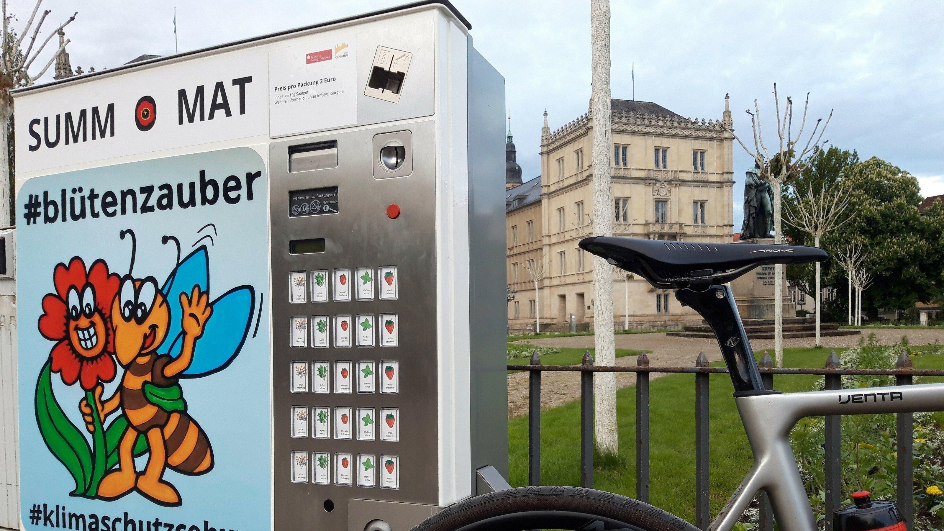 """Ein moderner Zigarettenautomat ist abgewandelt zum """"Summ-O-Mat"""", dessen Front die Comic-Zeichnung einer Biene ziert, die eine rote Blüte umarmt. Im Hintergrund Schloss Ehrenburg."""