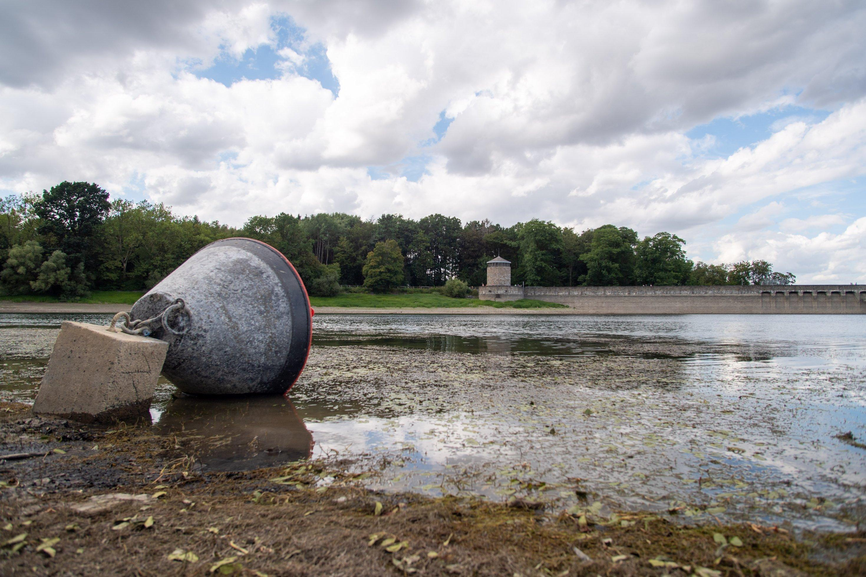 Eine Boje liegt in einem Staubecken bei Niedrigwasser auf dem Trockenen. Im Hintergrund Stauanlagen der Möhnetalsperre.