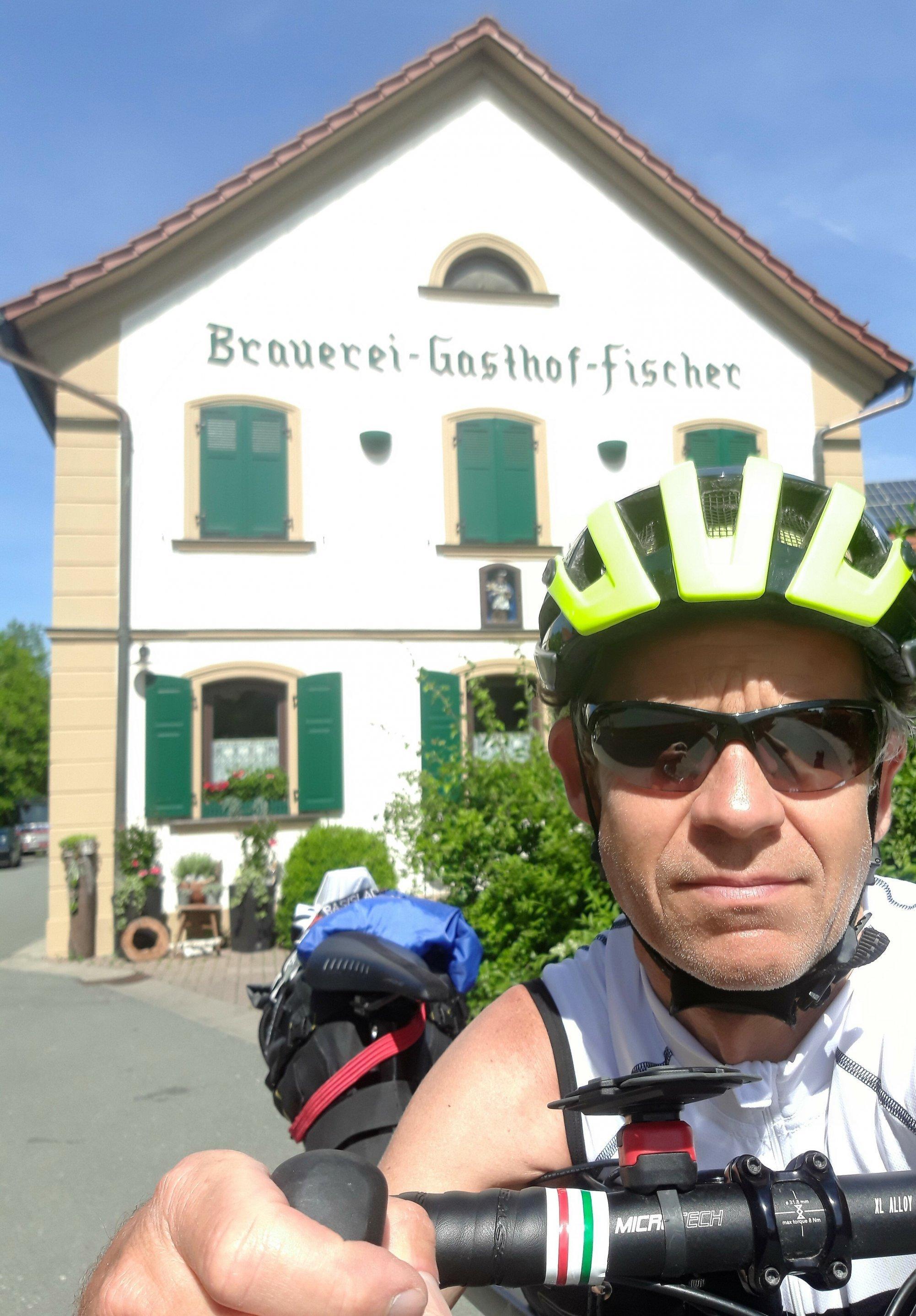 Selfie des Helm-bewehrten RadelndenReporters vor der weißen Hausfront der Brauerei, Aufschrift dort: Brauerei-Gasthof-Fischer.