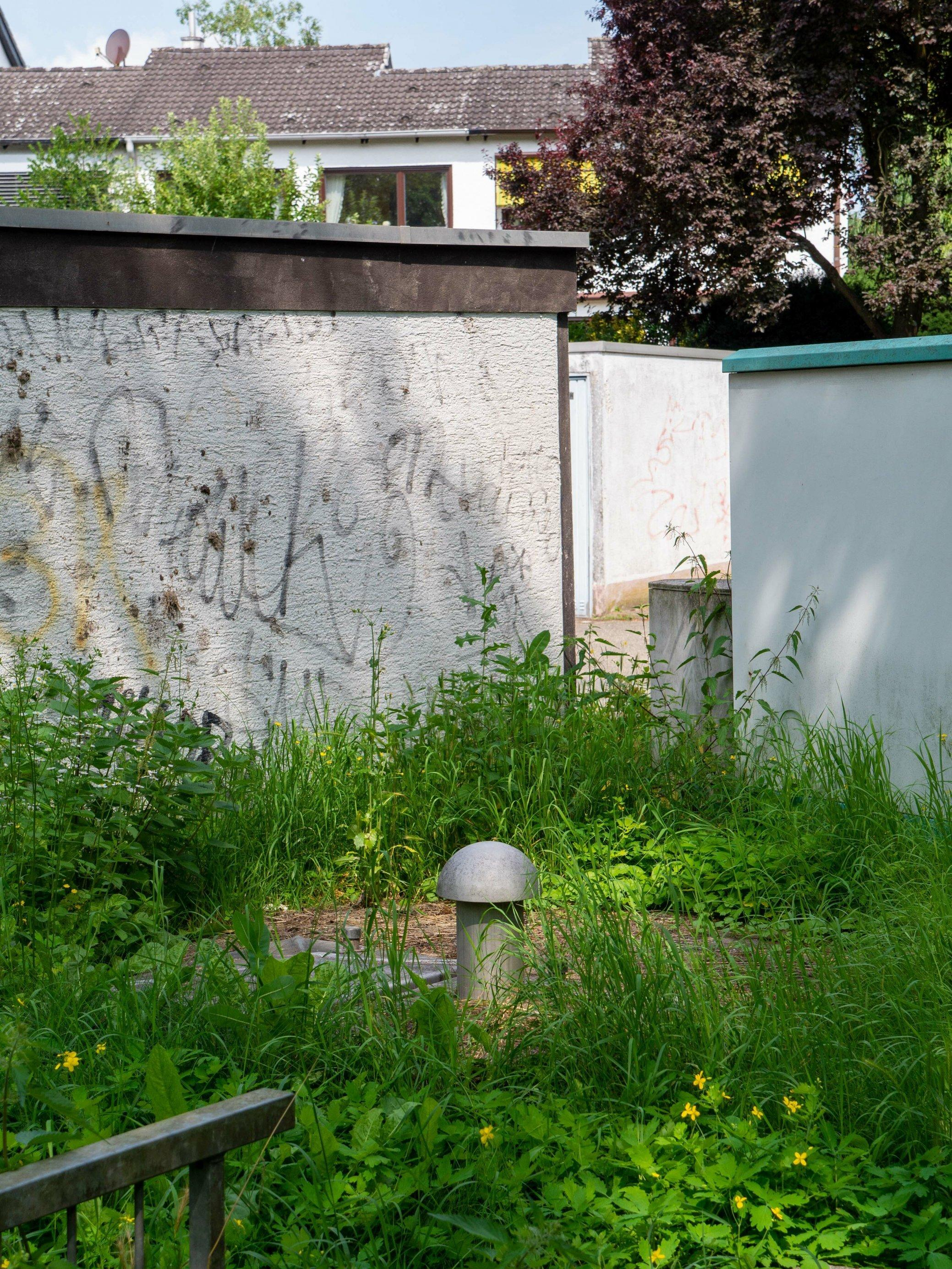 Am pilzförmigen Belüftungsstutzen ist einer der Brunnen hinter Garagenwänden zu erkennen, im Hintergrund Wohnhäuser