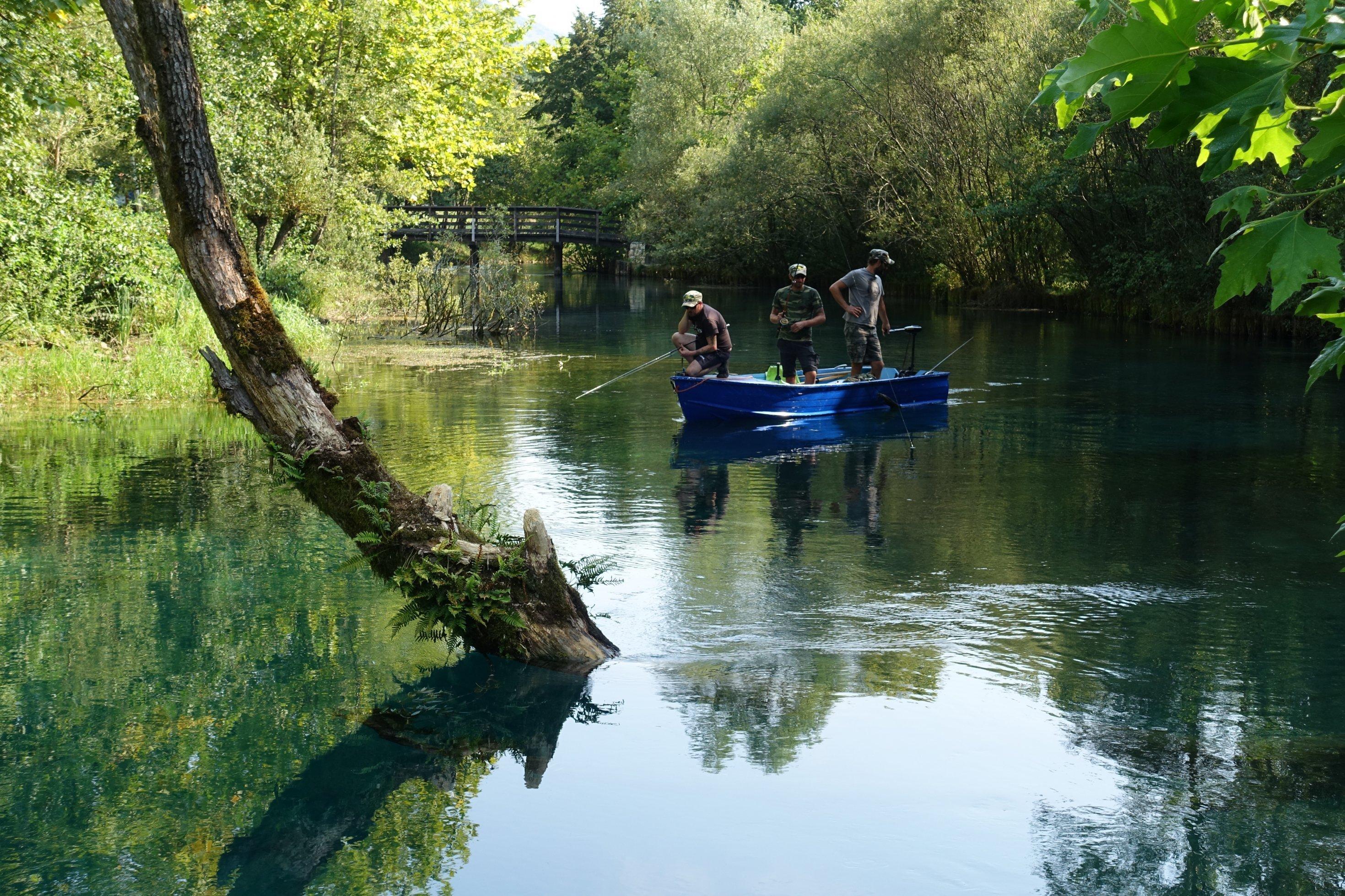 Fluss mit Bäumen, kleines Boot, darin Fischer, im Hintergrund eine Holzbrücke