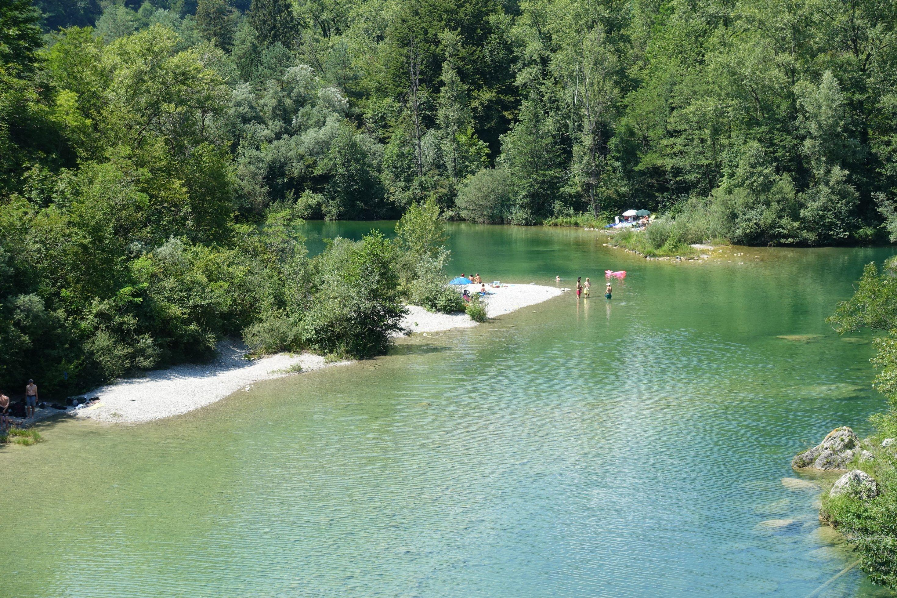 Kurve eines smaragdgrünen Flusses, rundum viel Wald, im Wasser und am Kiestrand Menschen in Badekleidung.