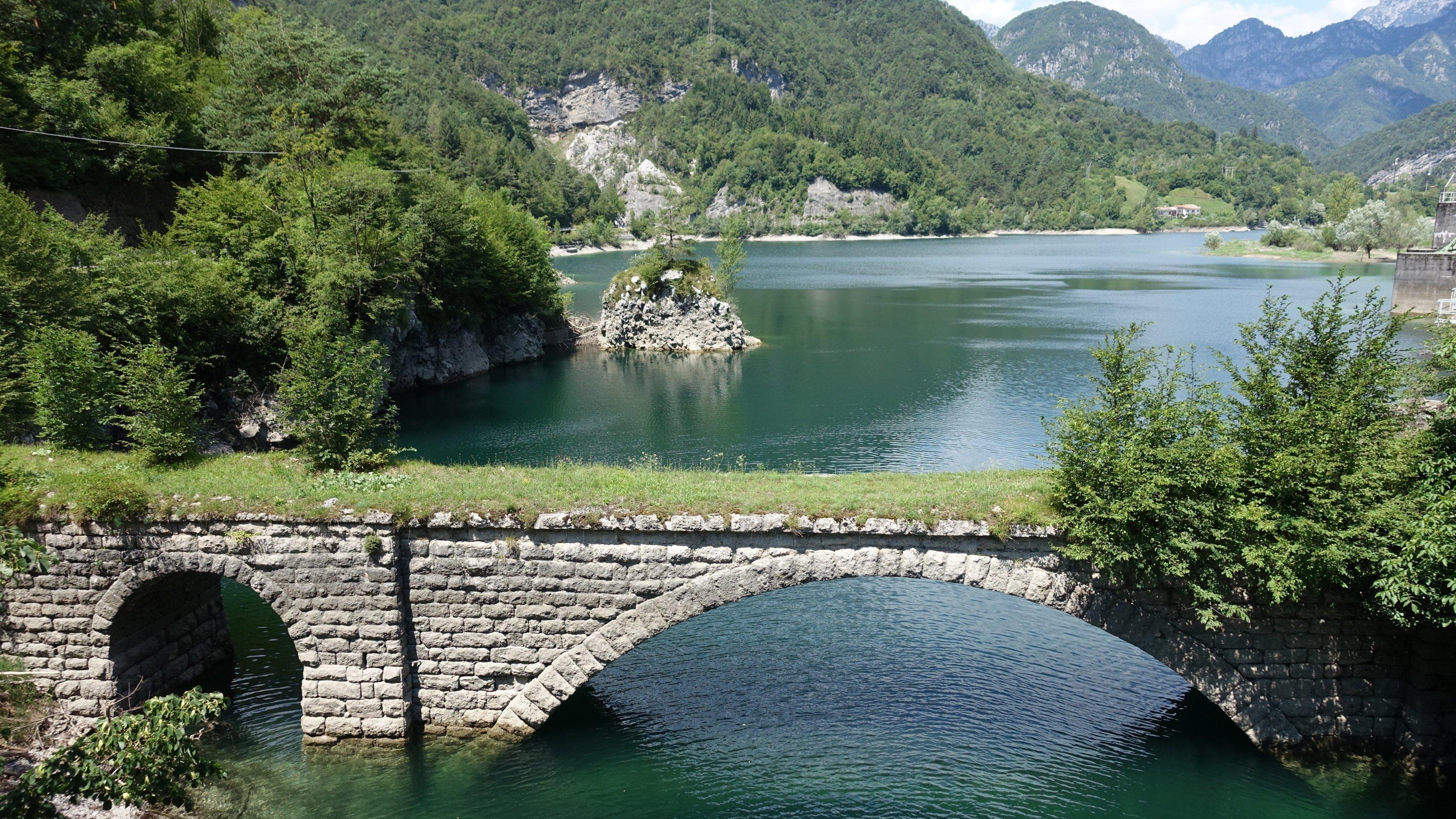 Stausee des Flusses Meduna, dahinter schroffe Berge mit Wald, vorne eine alte Steinbrücke