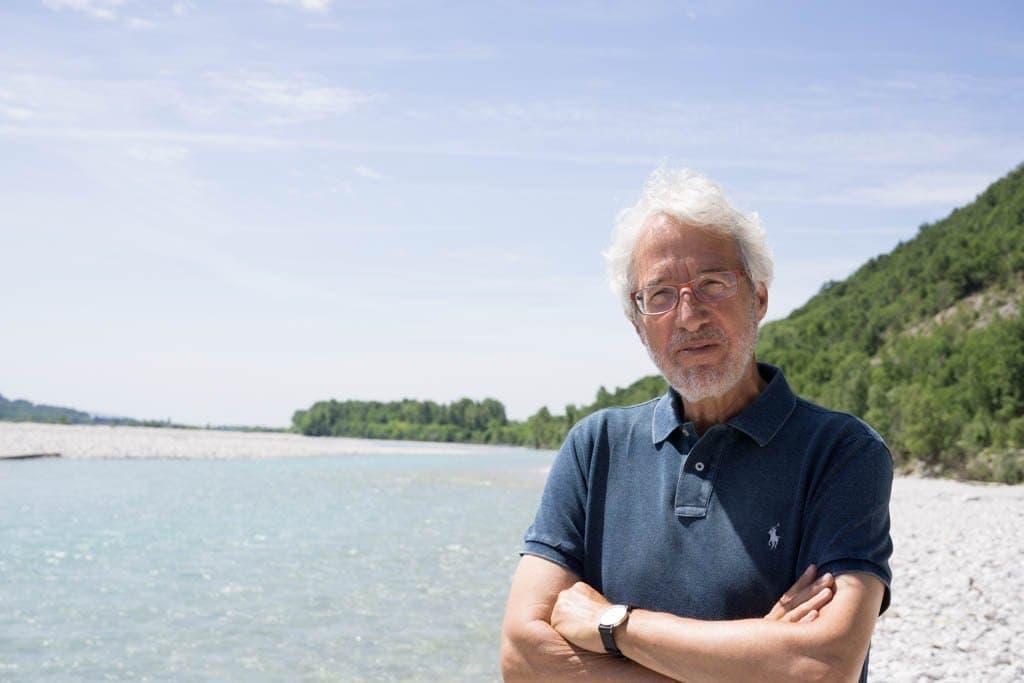 Mann mit weißem Haar und Vollbart steht an Fluss mit viel Schotter und türkisfarbenem Wasser.