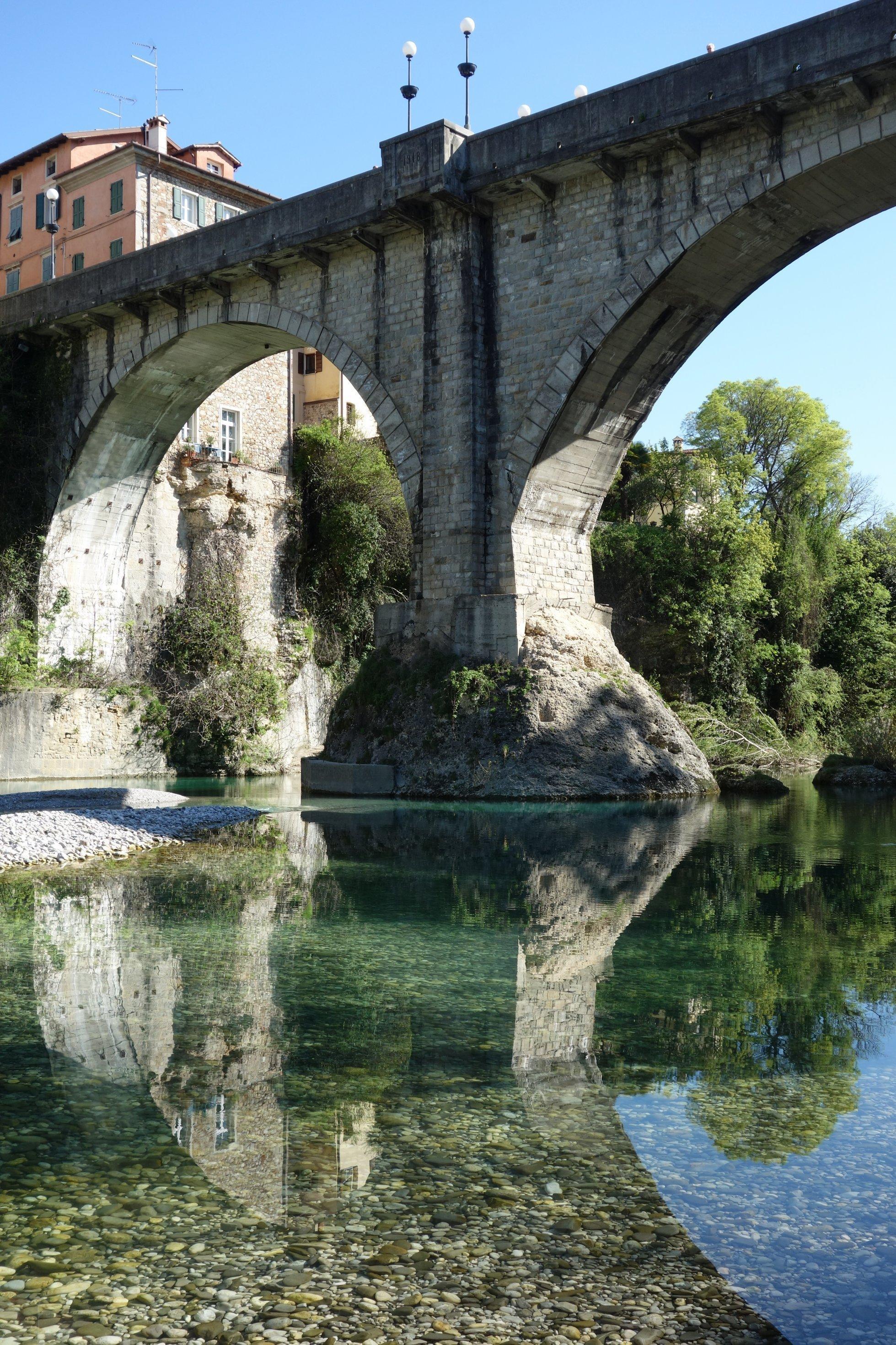 Mächtige alte Brücke aus Stein, darunter ein ganz klarer grüner Fluss, links oben an der Brücke ein altes italienisches Haus.