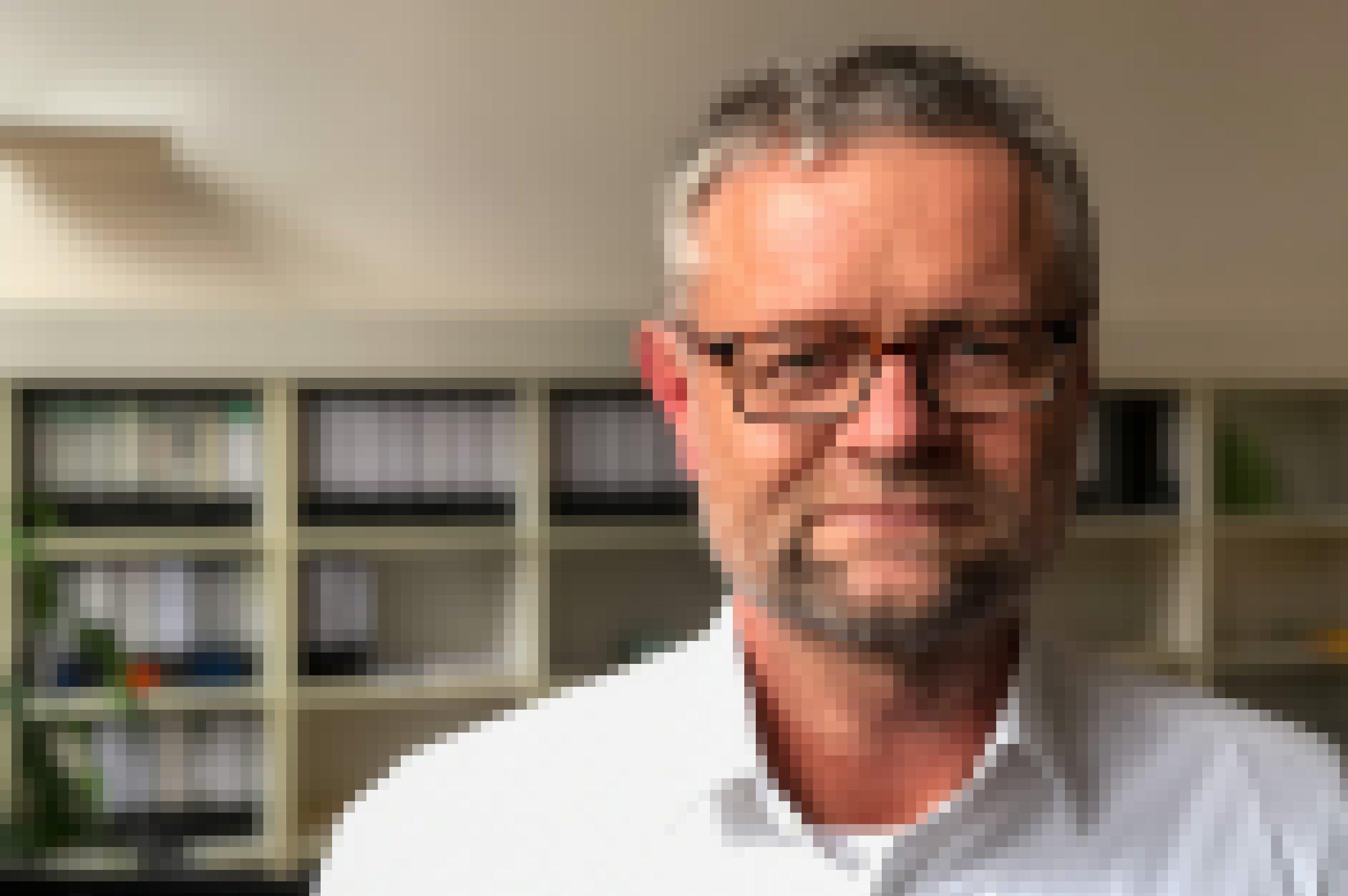 Ein Mann mit eckiger Brille und Drei-Tage-Bart schaut in die Kamera.