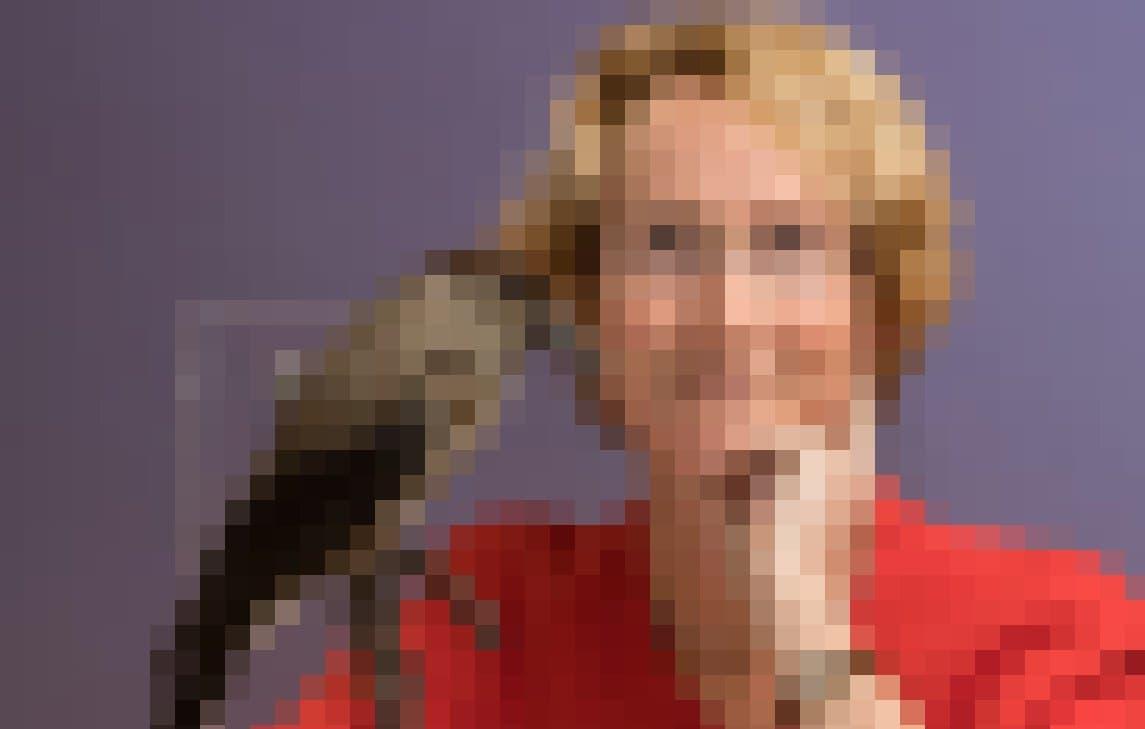 Eine blonde Frau schaut in die Kamera, die linke Hand am Kinn.